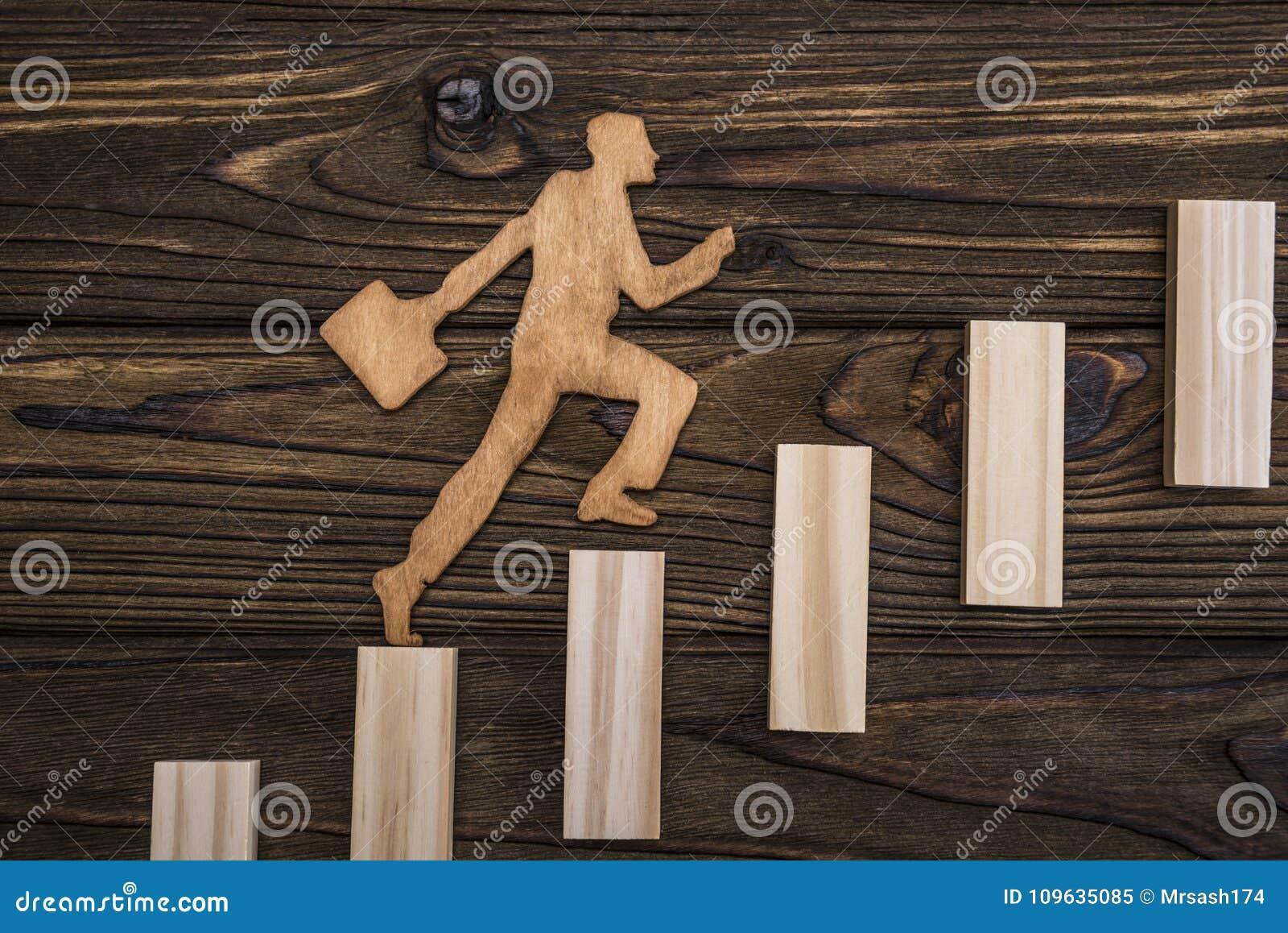 Силуэт от естественного дерева Бизнесмен с портфолио поднимает вверх лестницы его карьеры