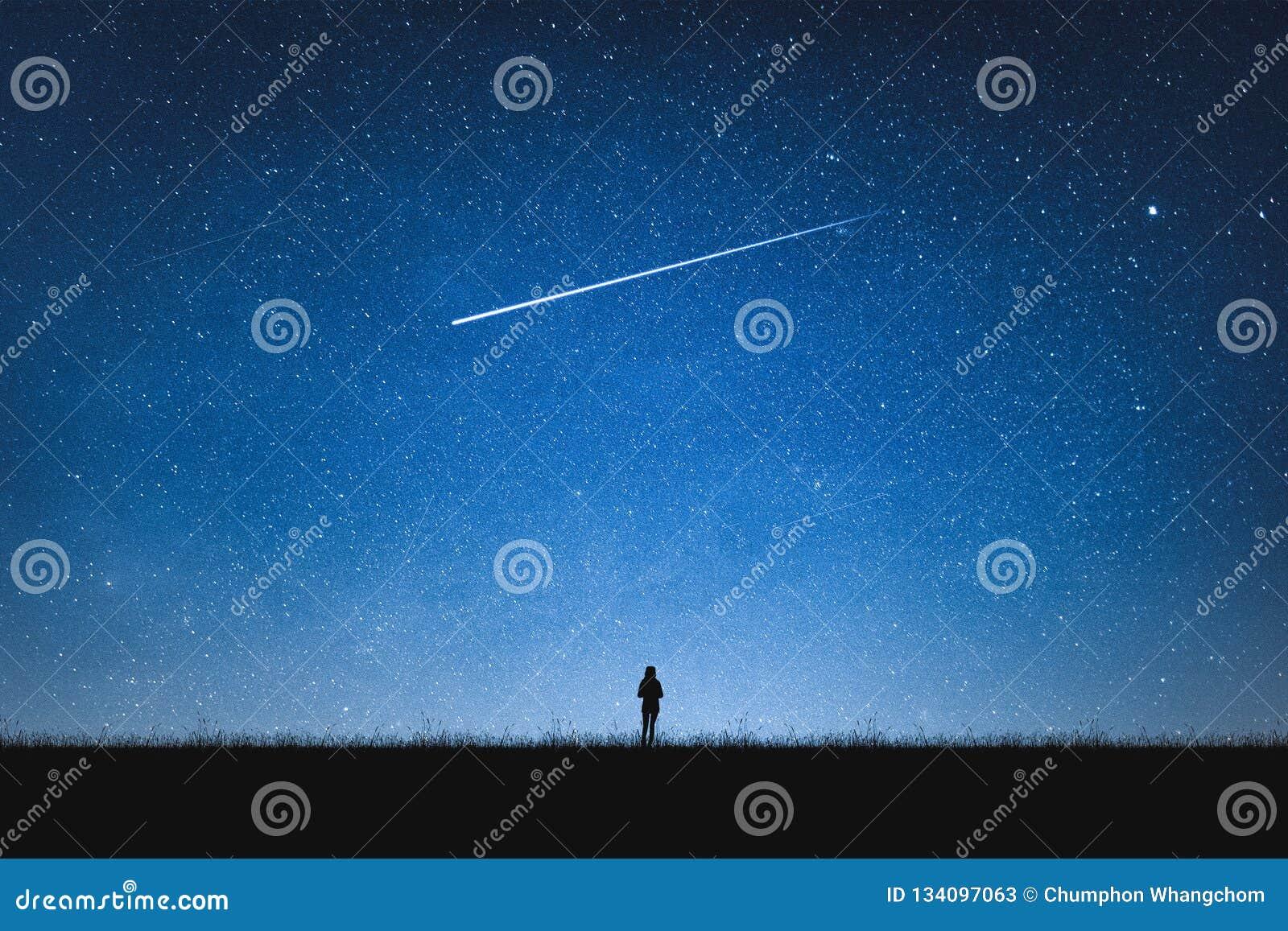 Силуэт положения девушки на горе и ночном небе со звездой стрельбы одна концепция