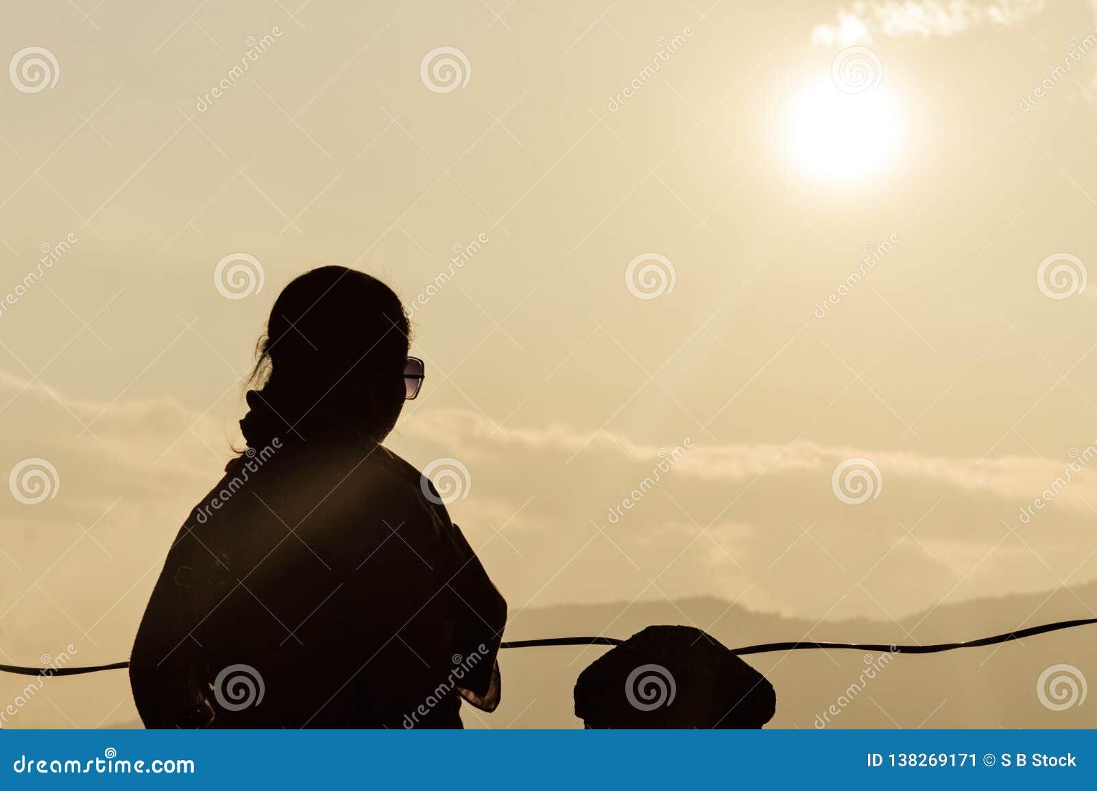Силуэт свободной спокойной расслабляющей женщины наслаждаясь свободой на заходе солнца на горе в утре в чистом счастье в точке от