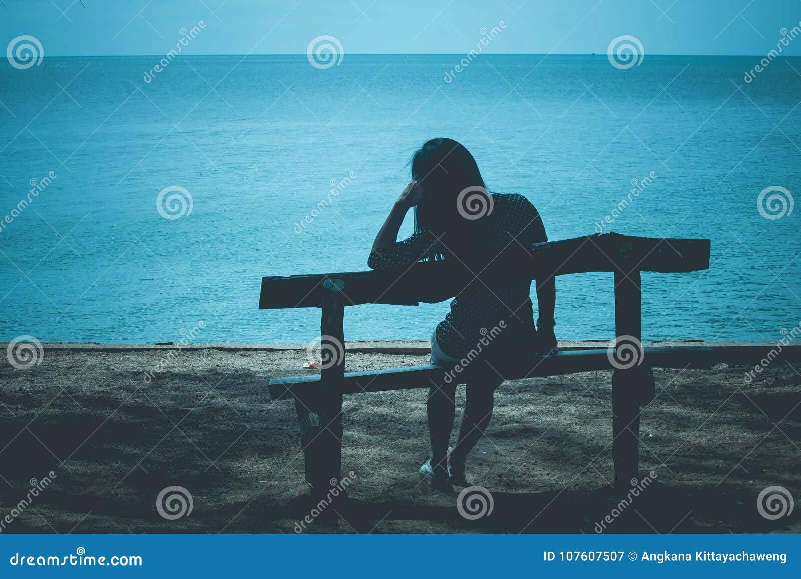 Силуэт сиротливой женщины сидя на деревянной скамье на пляже и смотря к голубому морю