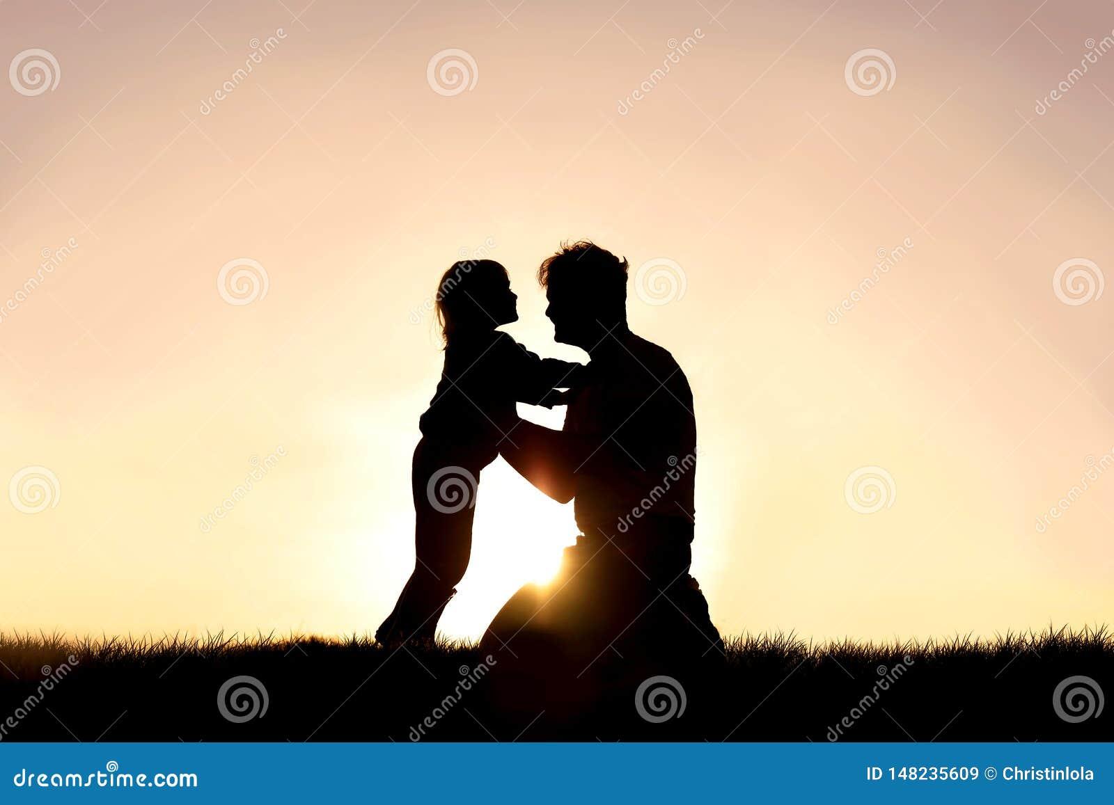 Силуэт счастливого отца и его маленького ребенка усмехаясь и играя на заходе солнца
