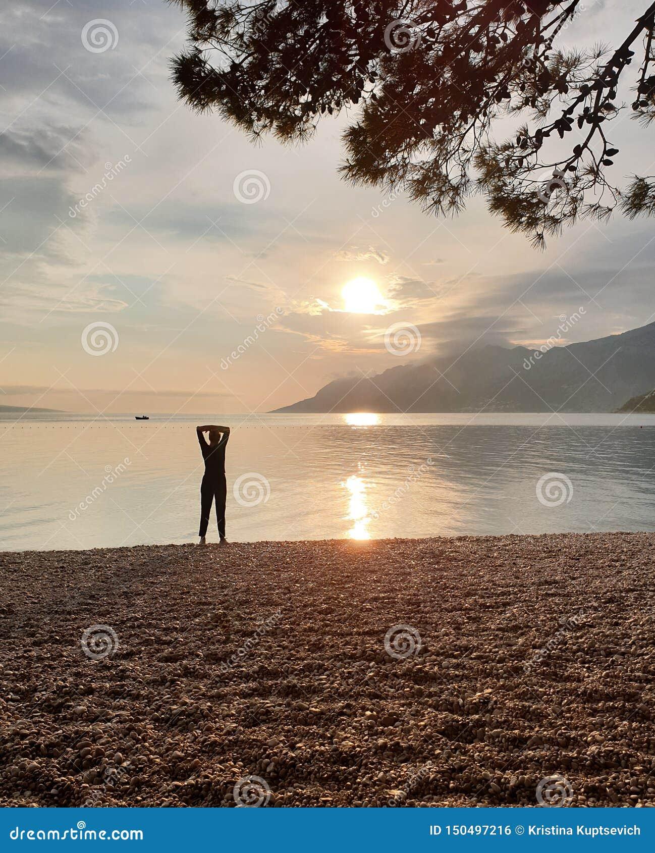 Силуэт худенькой женщины смотря заход солнца, который стоит на seashore Наслаждаться расслабляющими летними каникулами