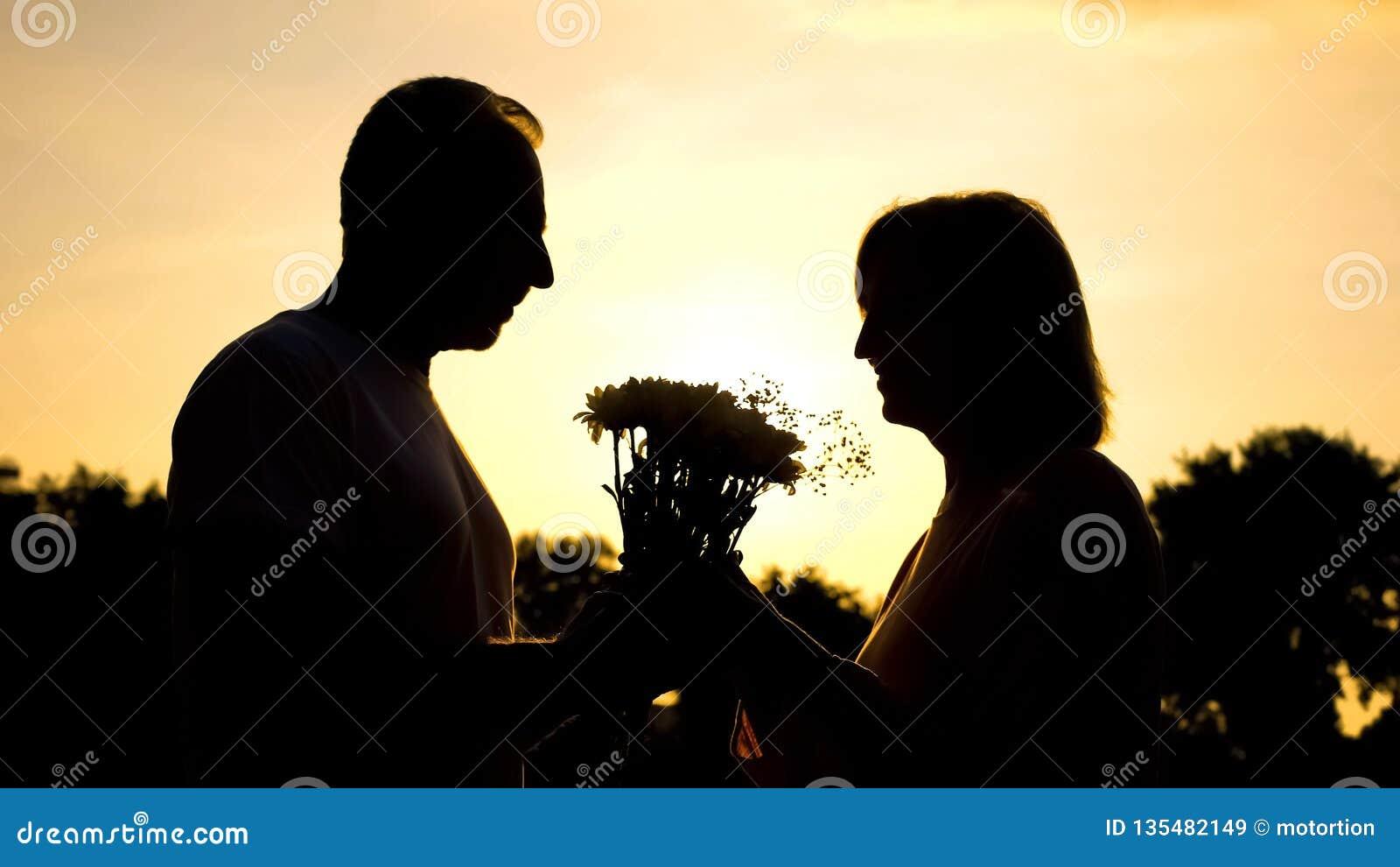 Силуэт человека давая цветки женщине, приятному сюрпризу, счастью старости