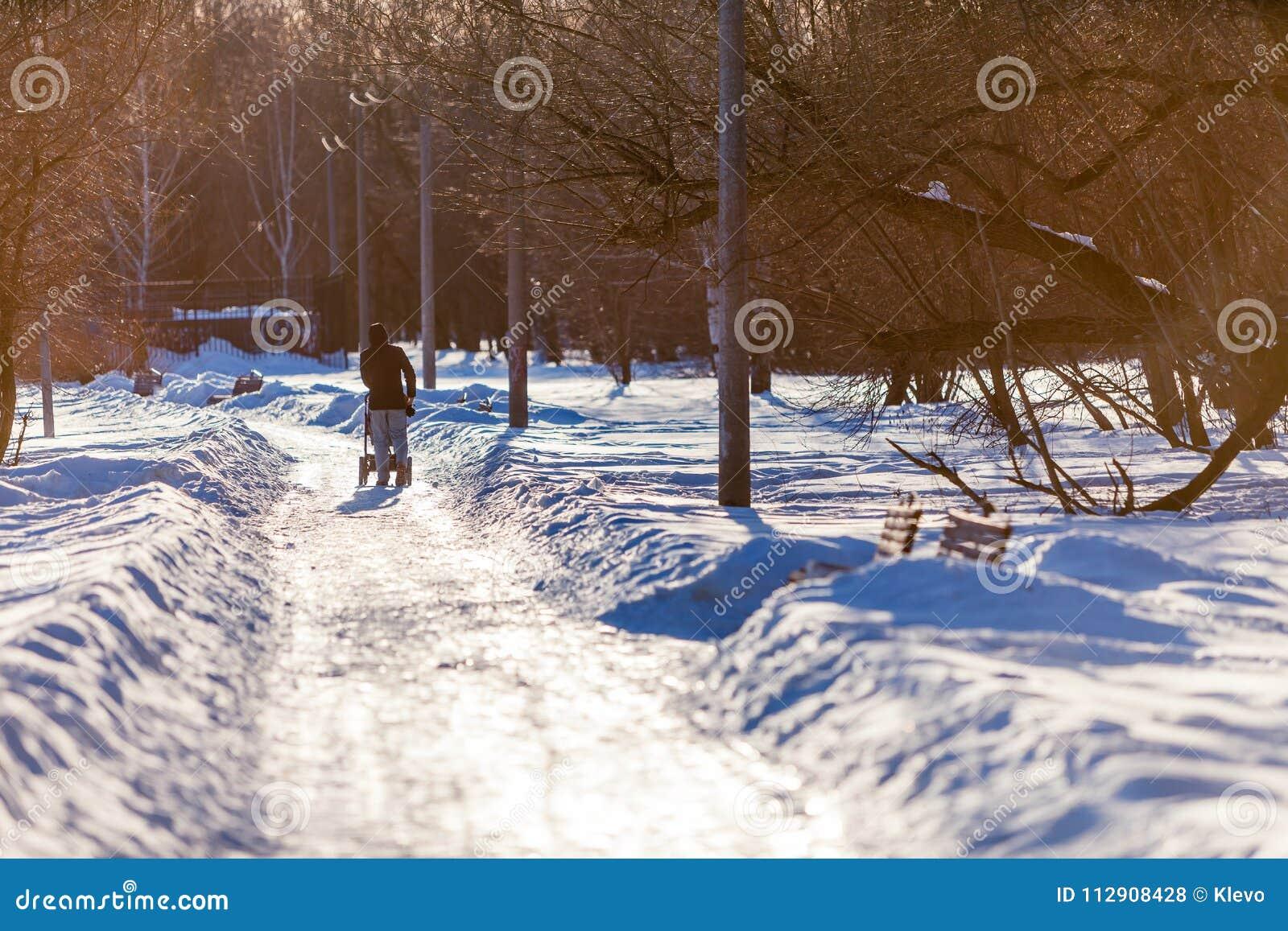 Силуэт человека с прогулочной коляской гуляет вдоль покрытого снег бульвара парка освещенного лучами причаливая солнца в марте