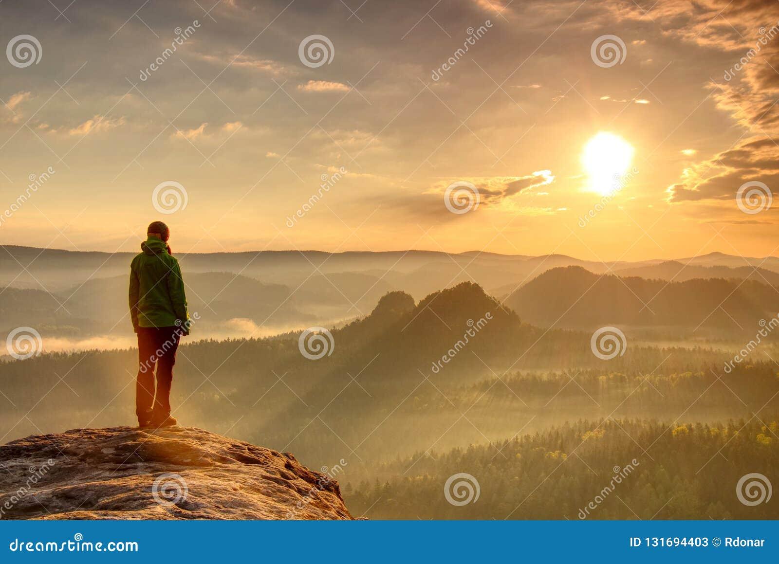 Силуэт hiker женщины в горах, заходе солнца и ландшафте падения Женский hiker рассматривая край на красивом заходе солнца