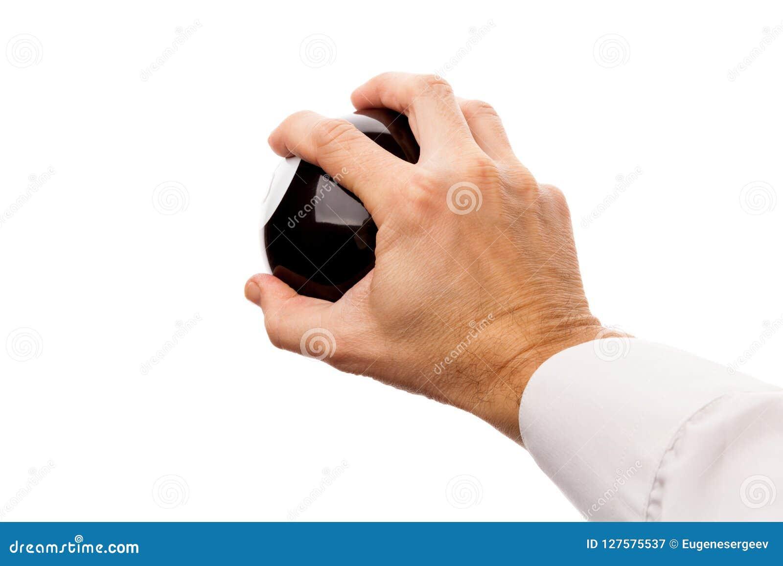 Сильная мужская рука держит черную сферу