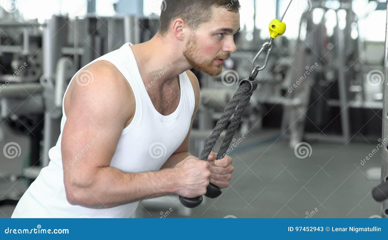 Сильный атлетический человек в футболке на тренировке спортзала на приборе блока Тренировка CrossFit