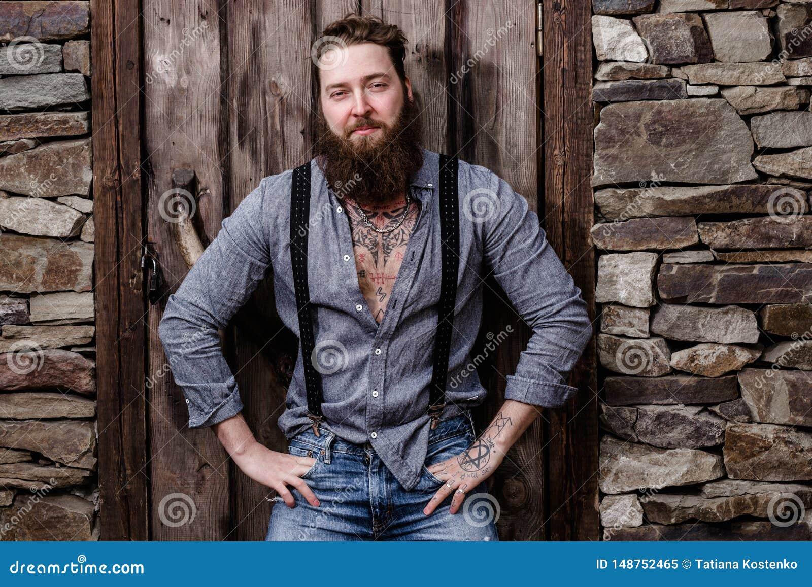Сильный зверский человек с бородой и татуировки на его руках одетых в стильных представлениях случайных одежд на предпосылку