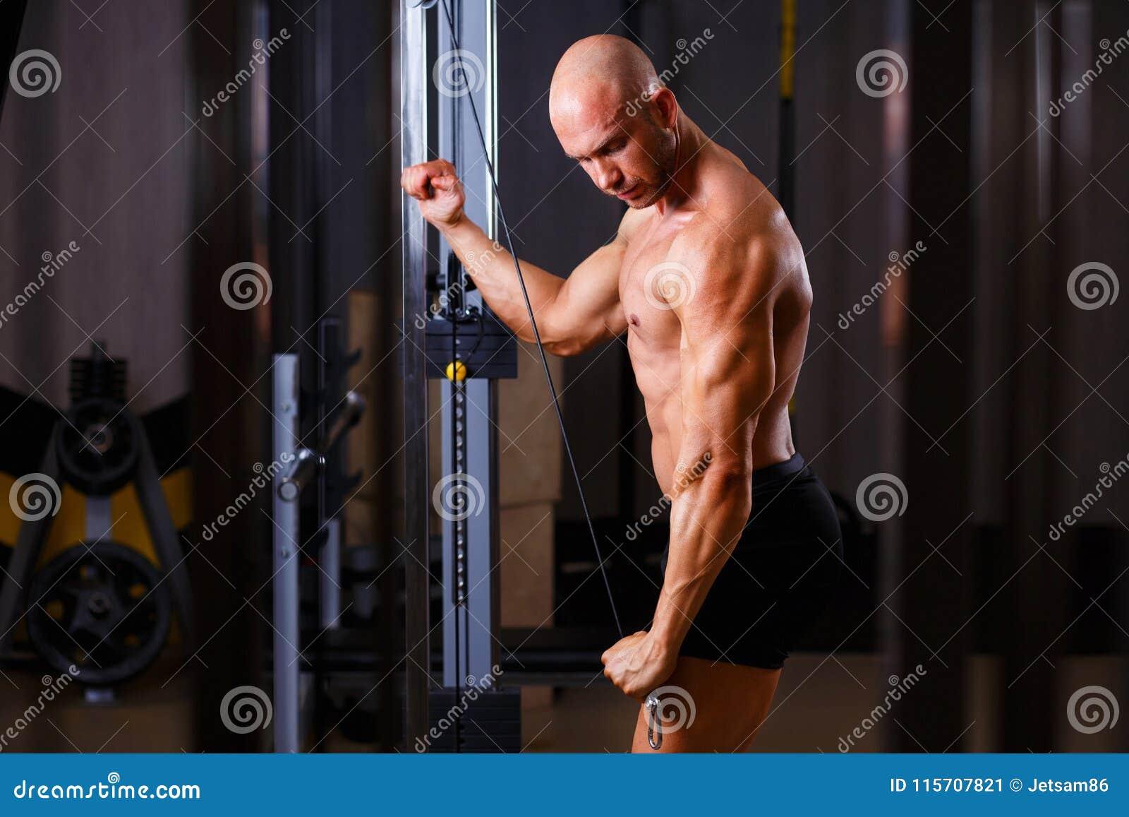 Сильный сорванный облыселый культурист человека разрабатывая с оборудованием внутри