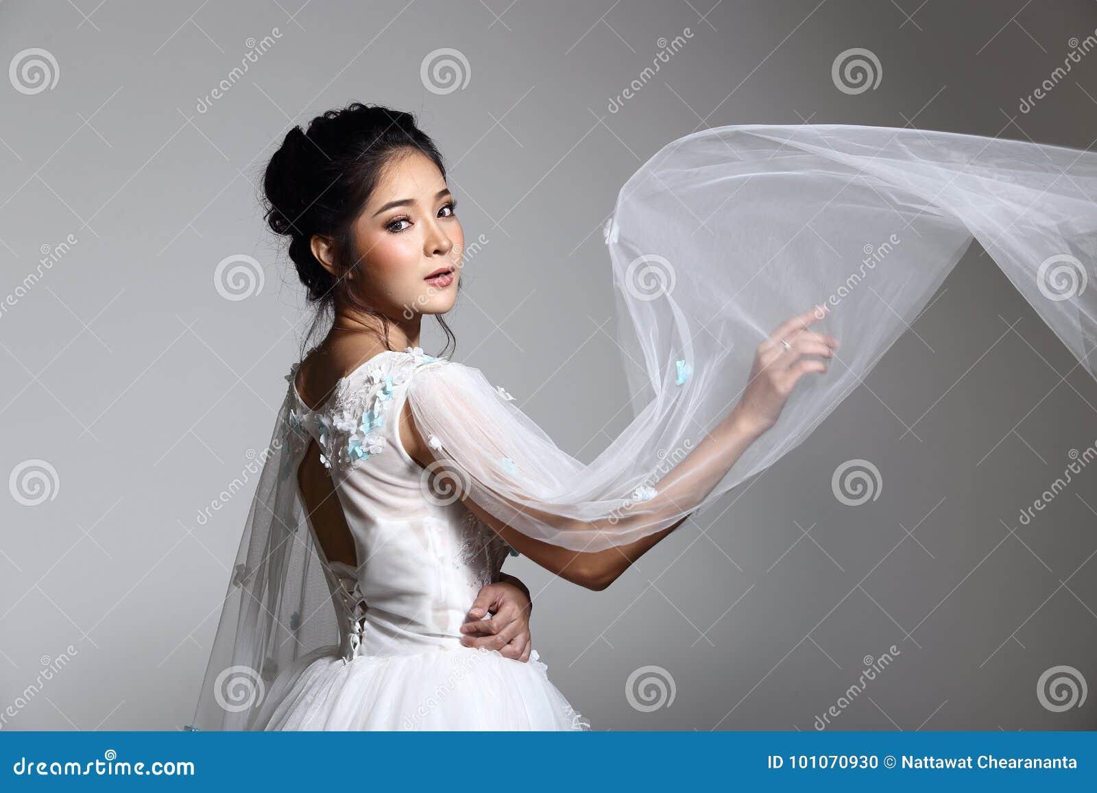 Симпатичная азиатская красивая невеста женщины в белом платье w мантии свадьбы