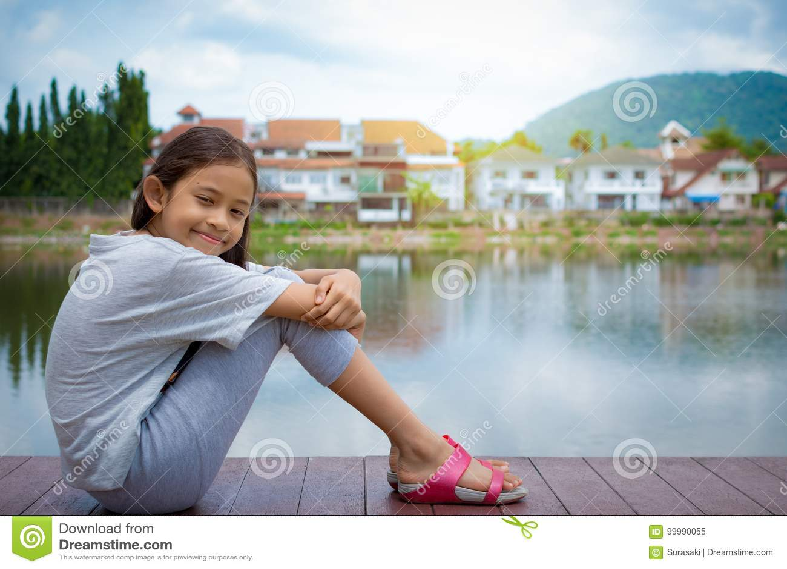 Симпатичная девушка сидя около естественного пруда с жилым массивом
