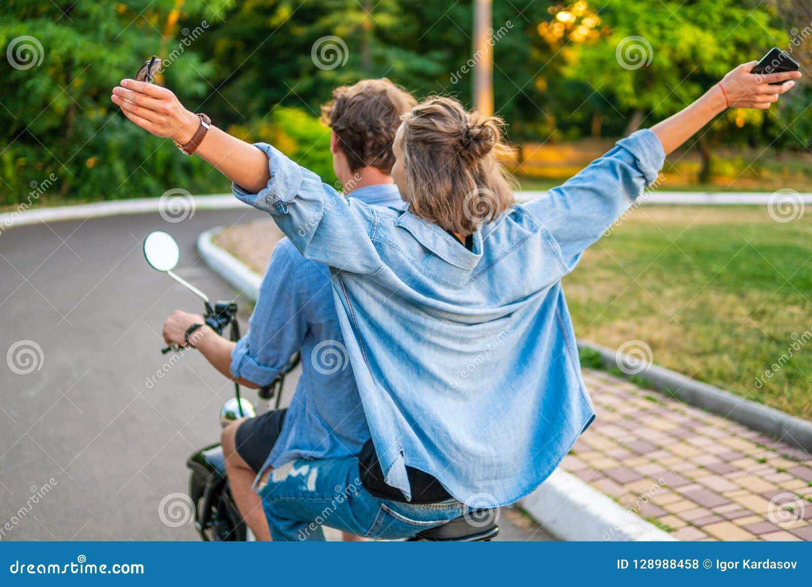 Симпатичные молодые пары управляя электрическим велосипедом во время лета