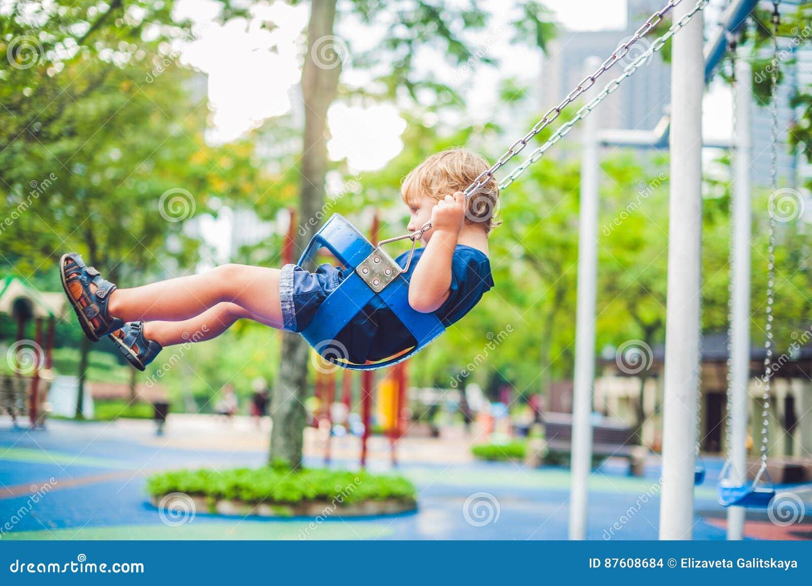Симпатичный белокурый мальчик на качании в парке Прелестный мальчик имея потеху на спортивной площадке