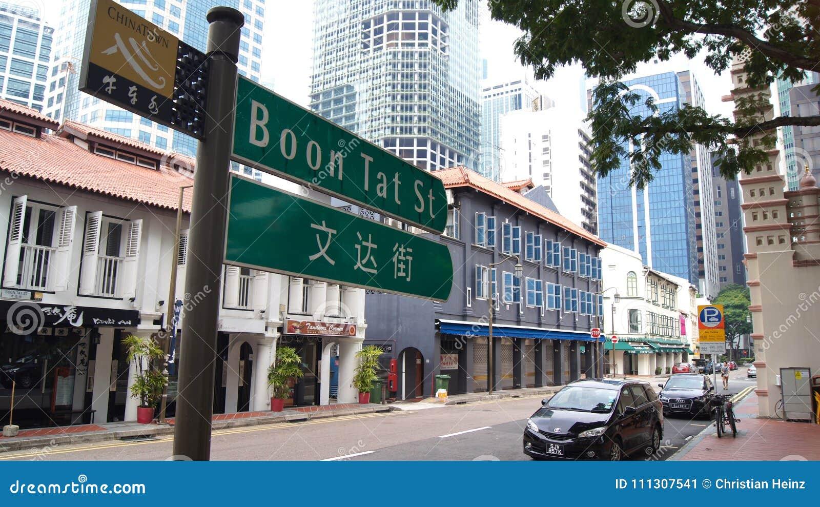 СИНГАПУР - 2-ое апреля 2015: Двуязычная улица подписывает внутри Сингапур Чайна-таун Сингапур мульти-расовый город где английский