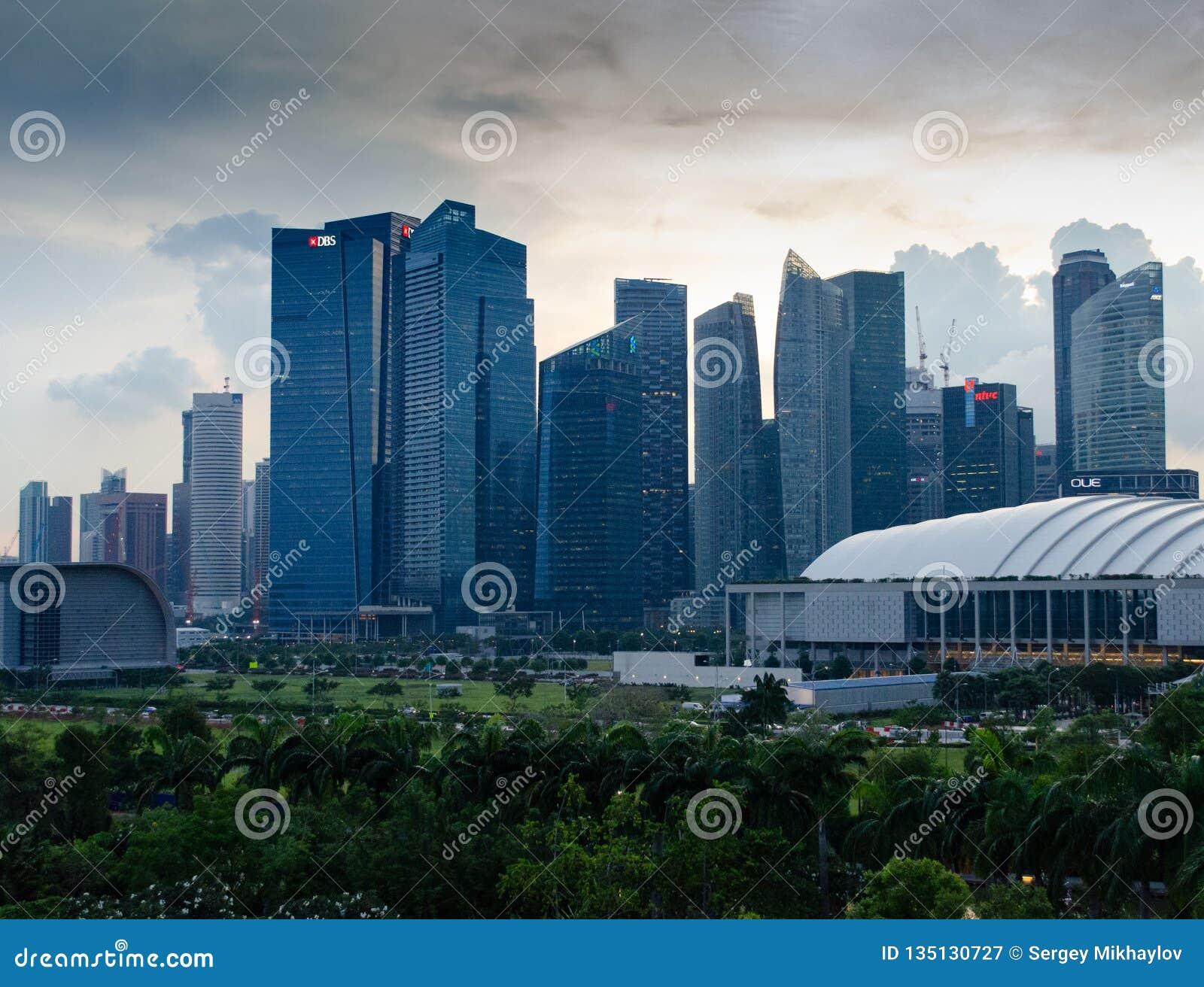 Сингапур - 28-ое апреля 2014: Небоскребы азиатского города на заходе солнца