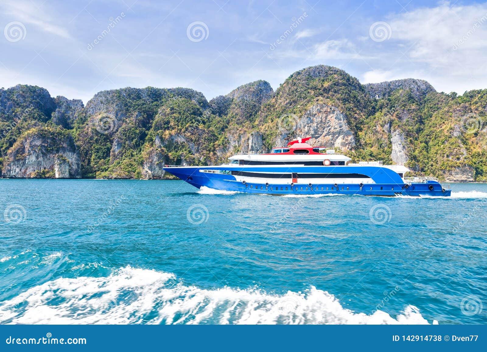 Синь с белой и красной шлюпкой скорости удовольствия акцентов Плавание на море против тропического острова горы Взгляд со стороны