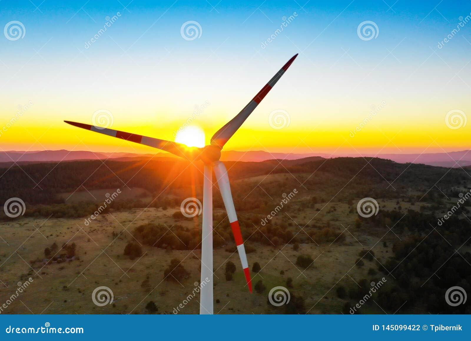 Сиротливая турбина ветрянки мирно поворачивая лезвия через ветер в красивом небе захода солнца