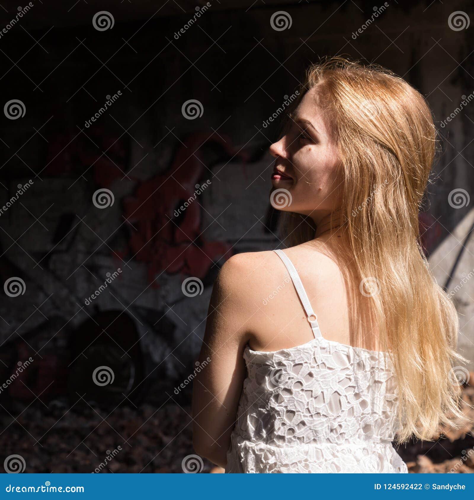 Сиротливая blondy женщина в блузке whit просвечивающей в покинутом здании