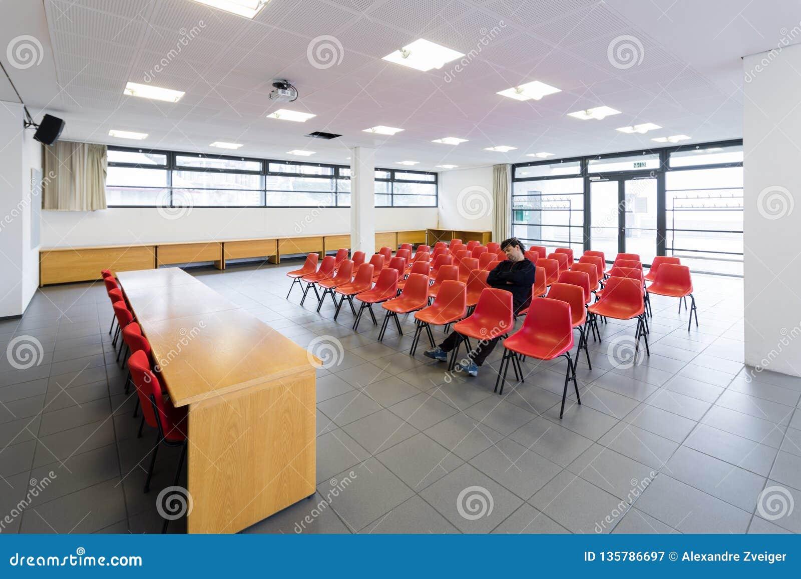 Сиротливый человек в пустом конференц-зале, концепции