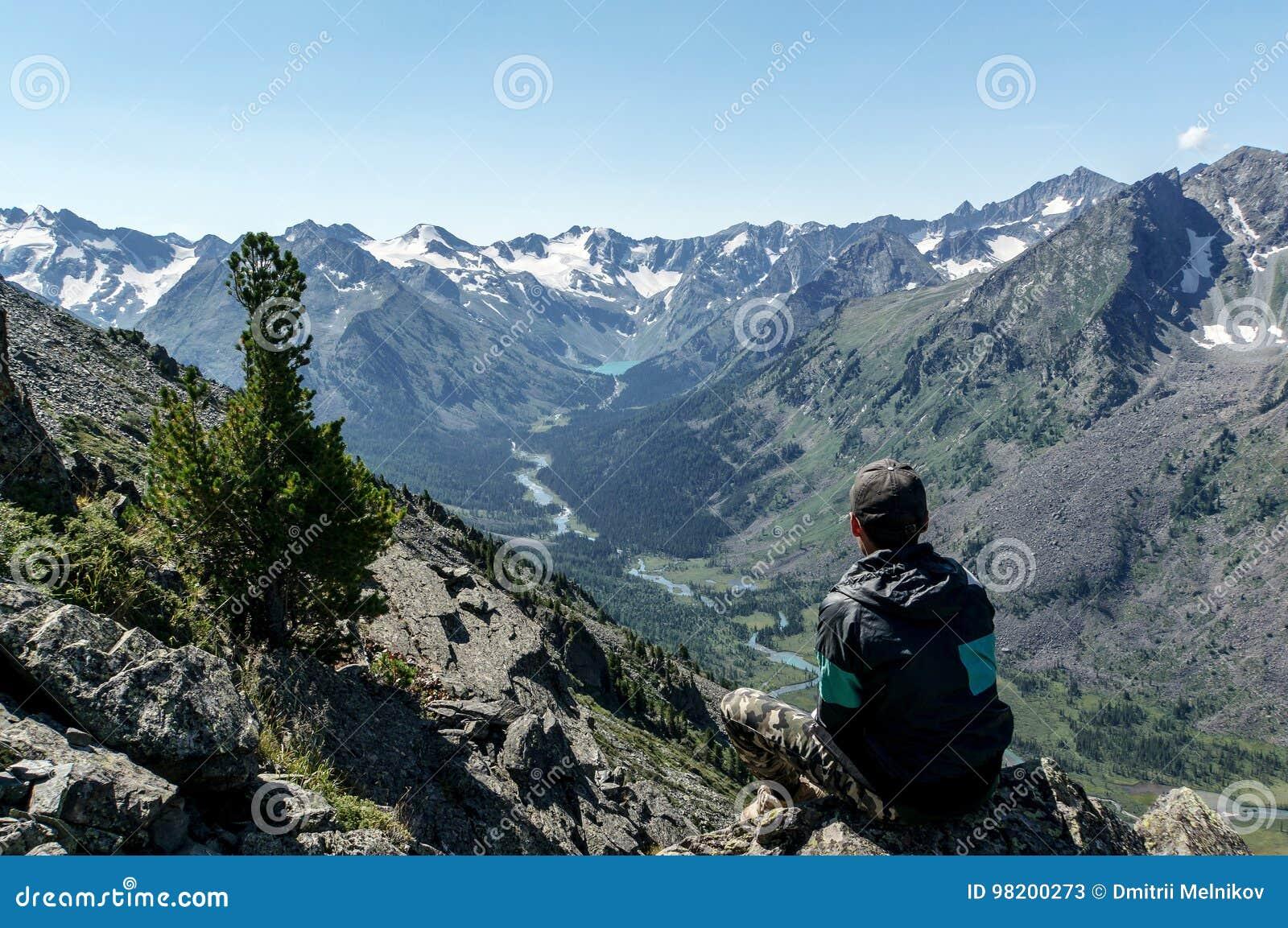 Download Сиротливый человек смотря River Valley сидя на утесе Редакционное Стоковое Фото - изображение насчитывающей скала, человек: 98200273