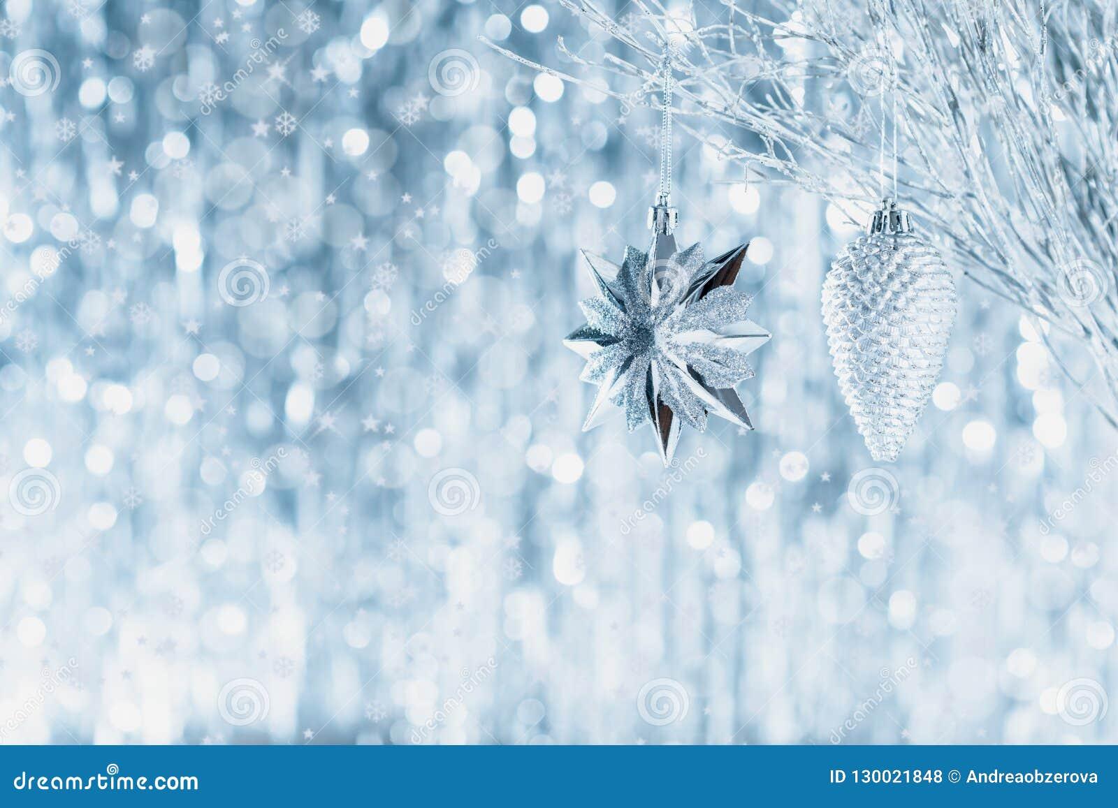 Сияющие серебряные орнаменты рождества вися на дереве, с defocused светами рождества на заднем плане звезды абстрактной картины к