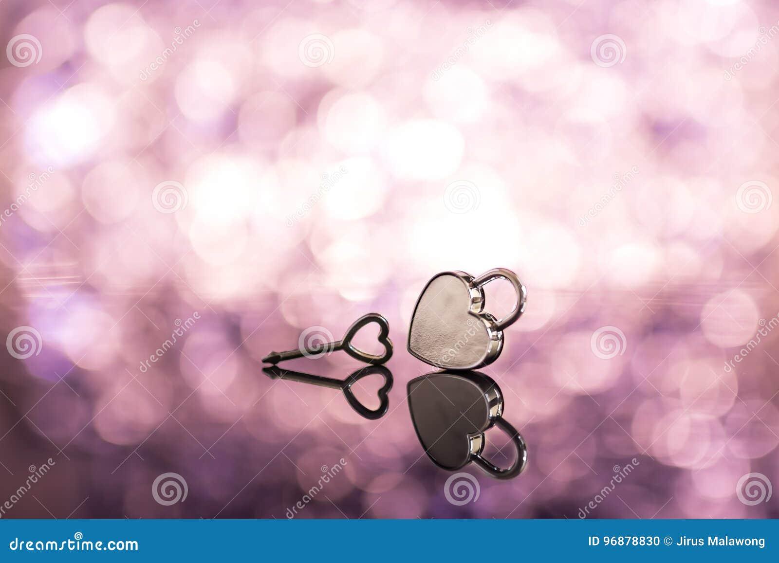 Сияющий замок и ключ сердца металла в розовом backgroun света и bokeh