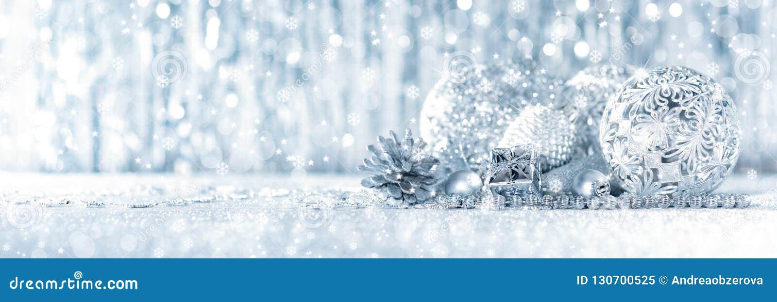 Сияющий серебряный подарок на рождество и красивые орнаменты, с defocused светами рождества на заднем плане
