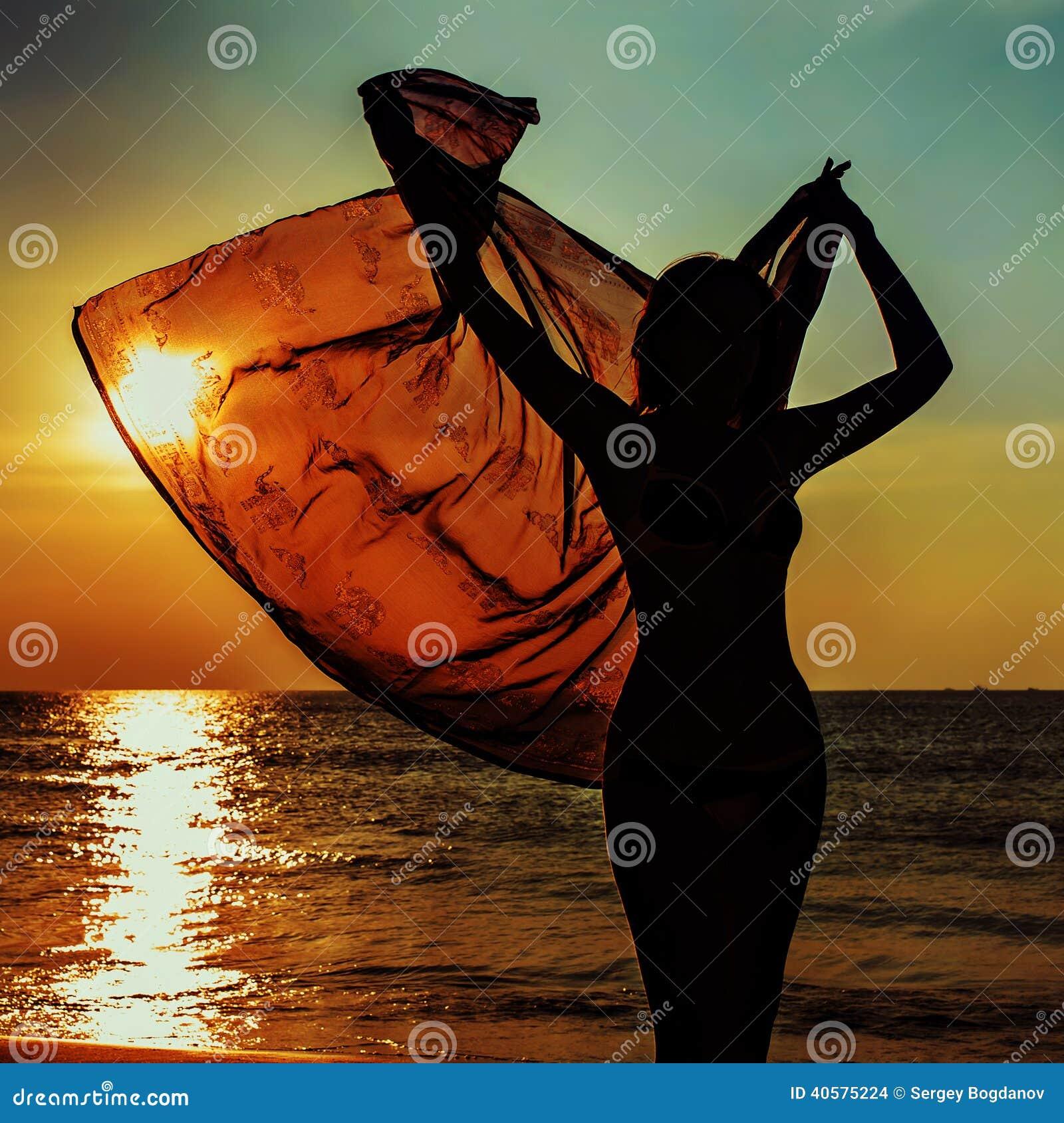 Силуэт девушки против моря захода солнца