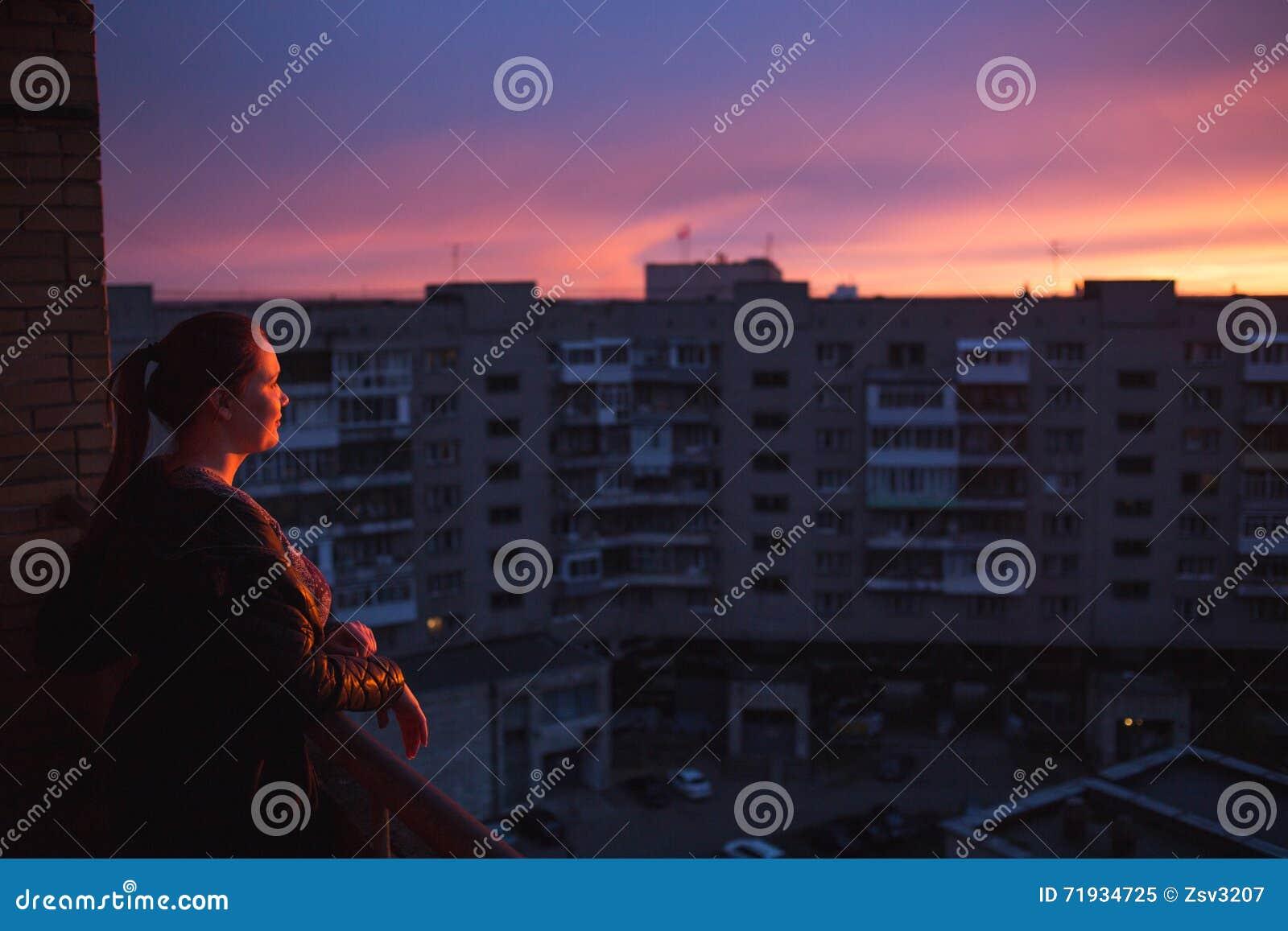 Силуэт женщины наслаждаясь видом на город на заходе солнца Концепция одиночества, вечности, выбора