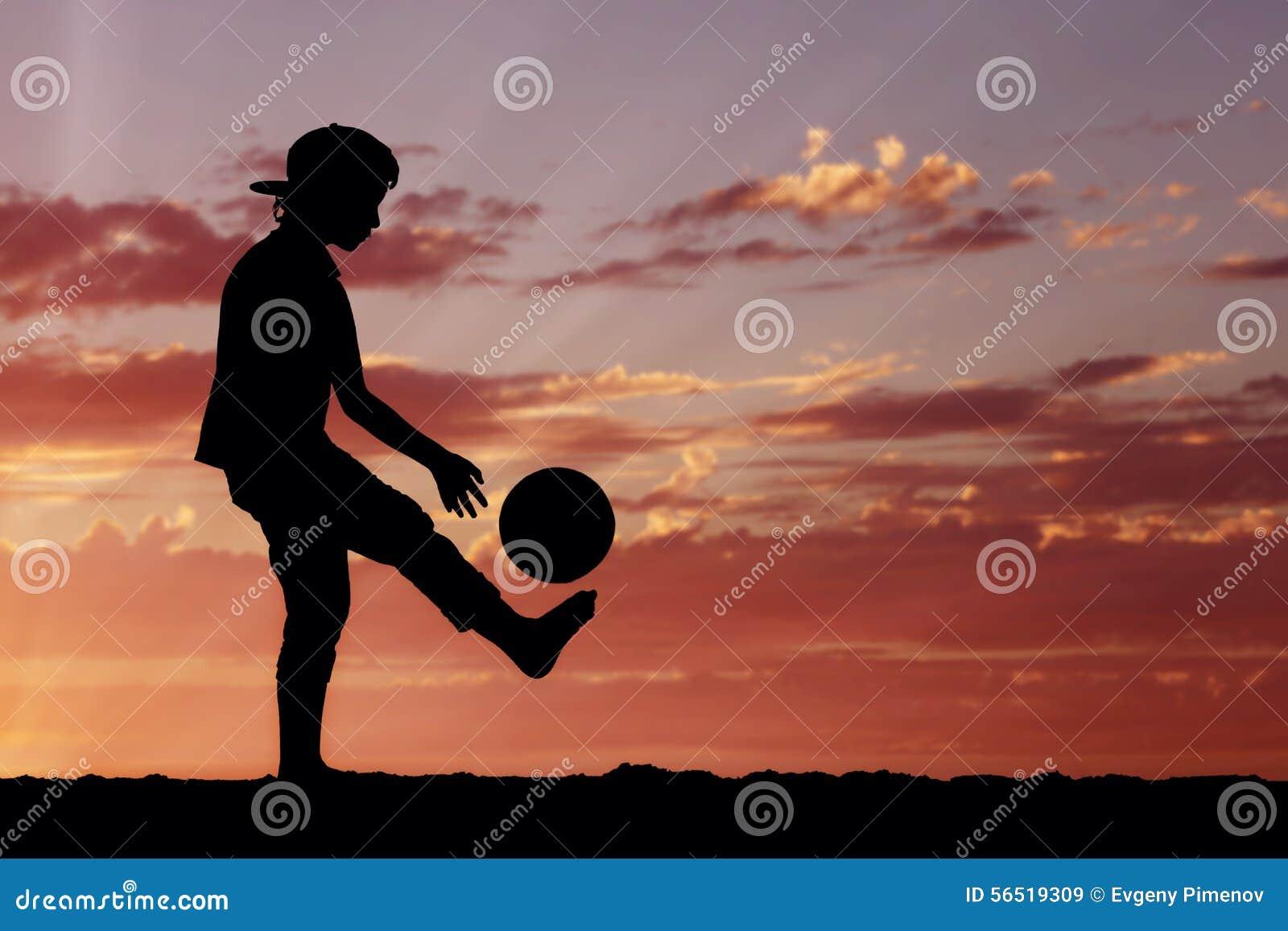 Силуэт мальчика играя футбол или футбол на