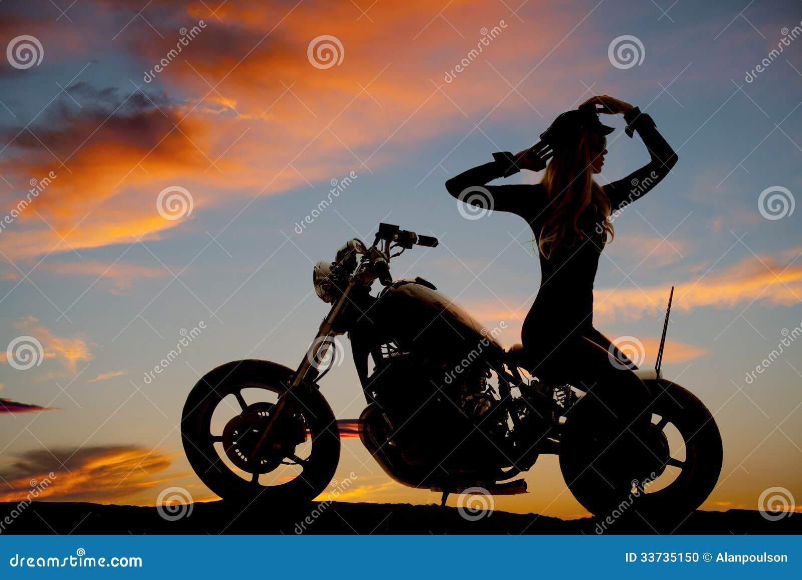Силуэт мотоцикла женщины сидит ОН назад руки вверх