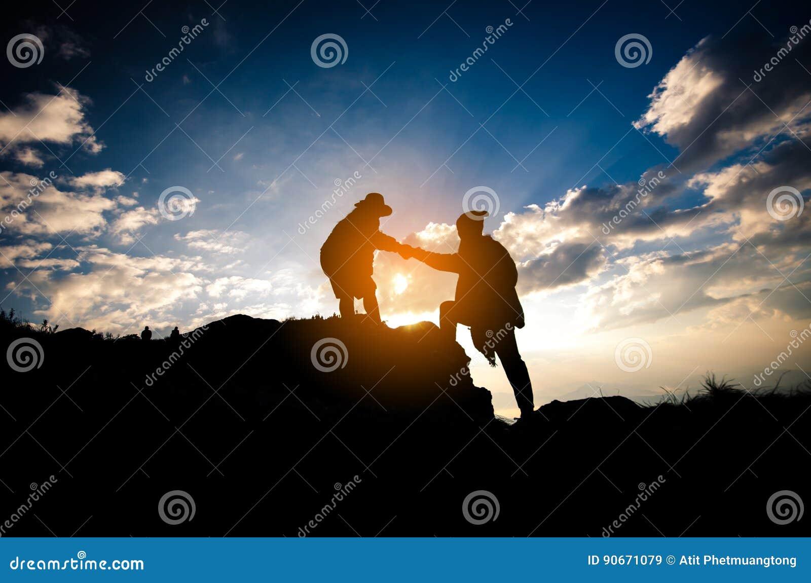 Силуэт персоны людей помогая на горе на утре