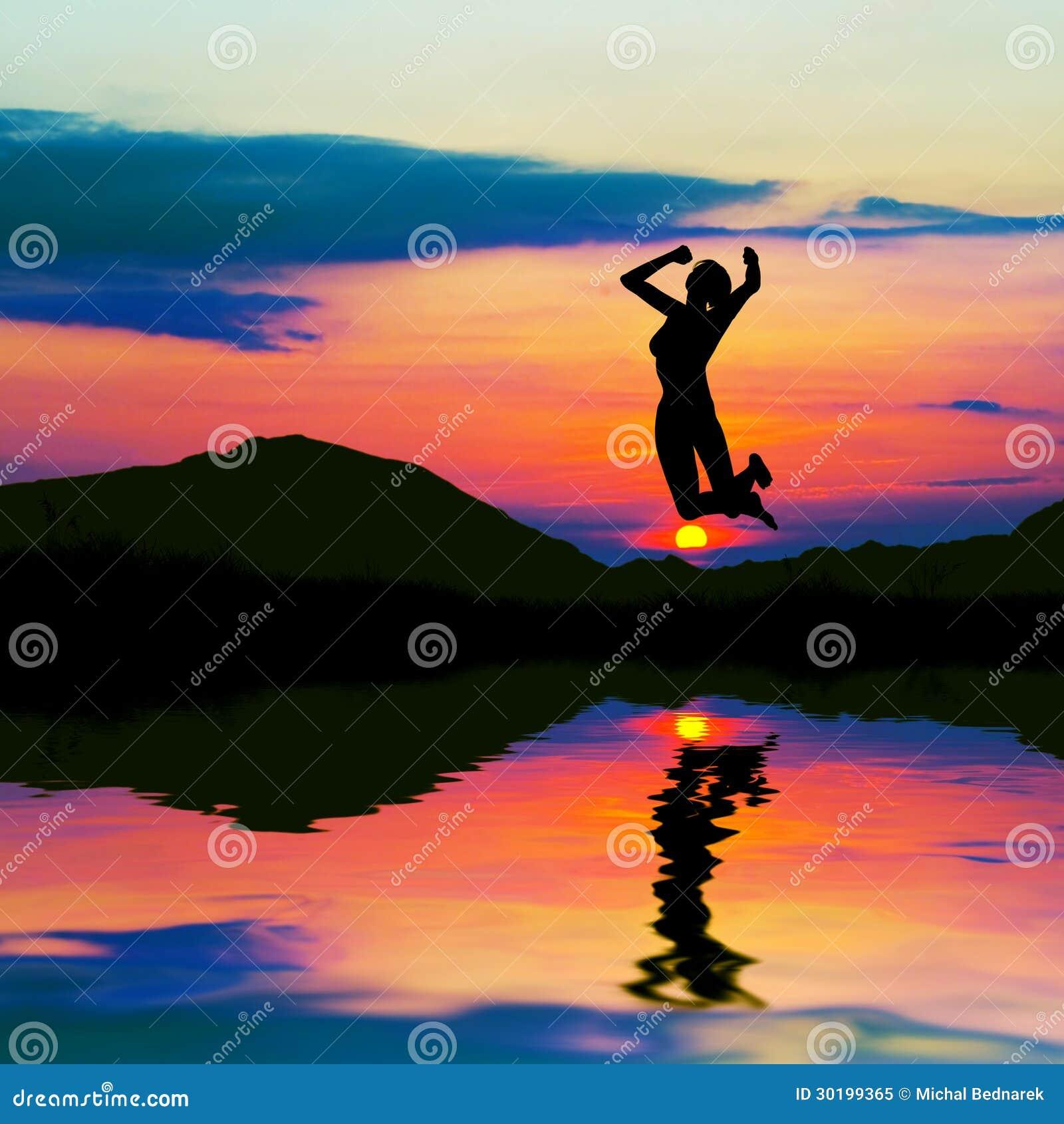 Силуэт счастливой женщины скача на заход солнца