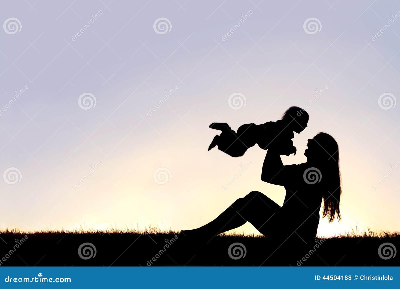 Силуэт счастливой матери играя снаружи с смеясь над младенцем