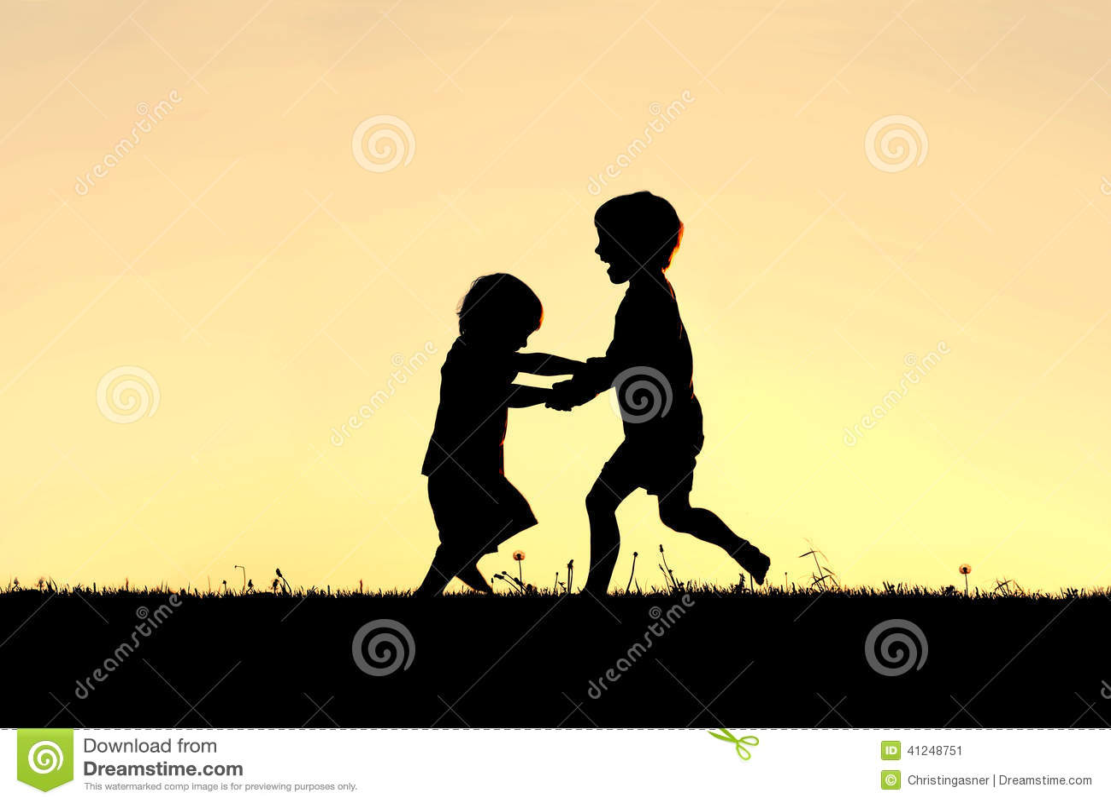 Силуэт счастливых маленьких детей танцуя на заходе солнца
