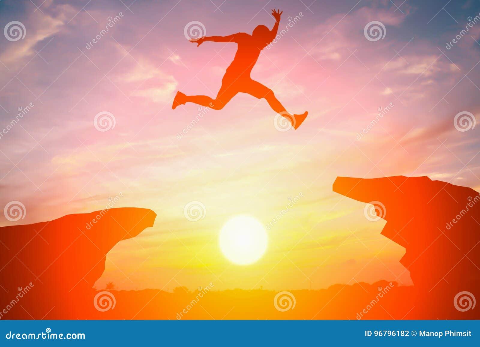 Силуэт человека скачет над скалой