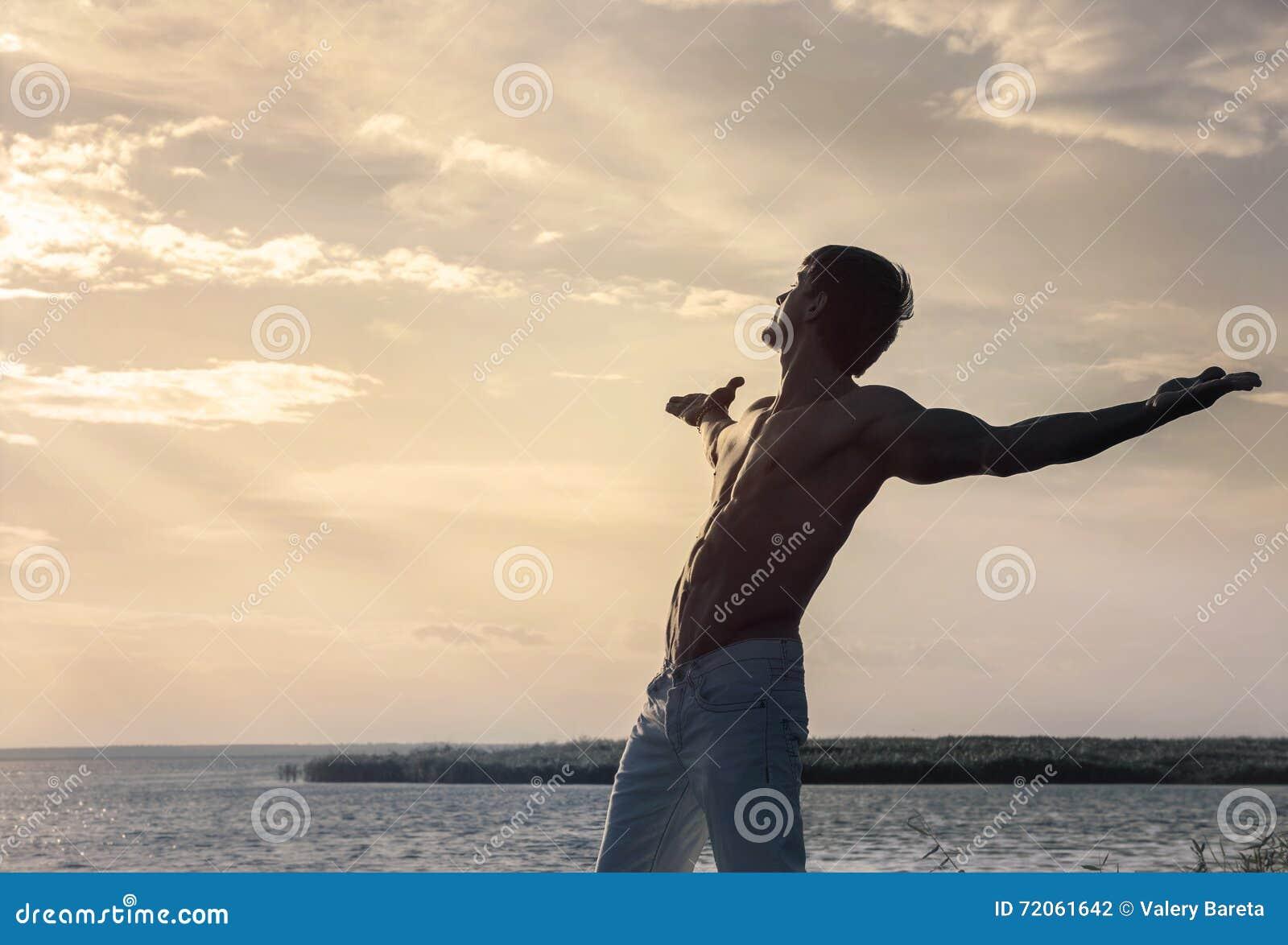 Силуэт человека с протягиванными оружиями на предпосылке неба