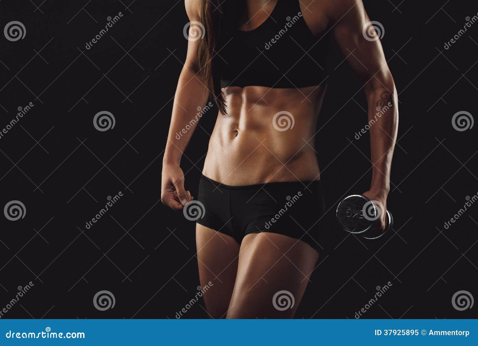 Сильная и мышечная женщина строения работая с гантелью
