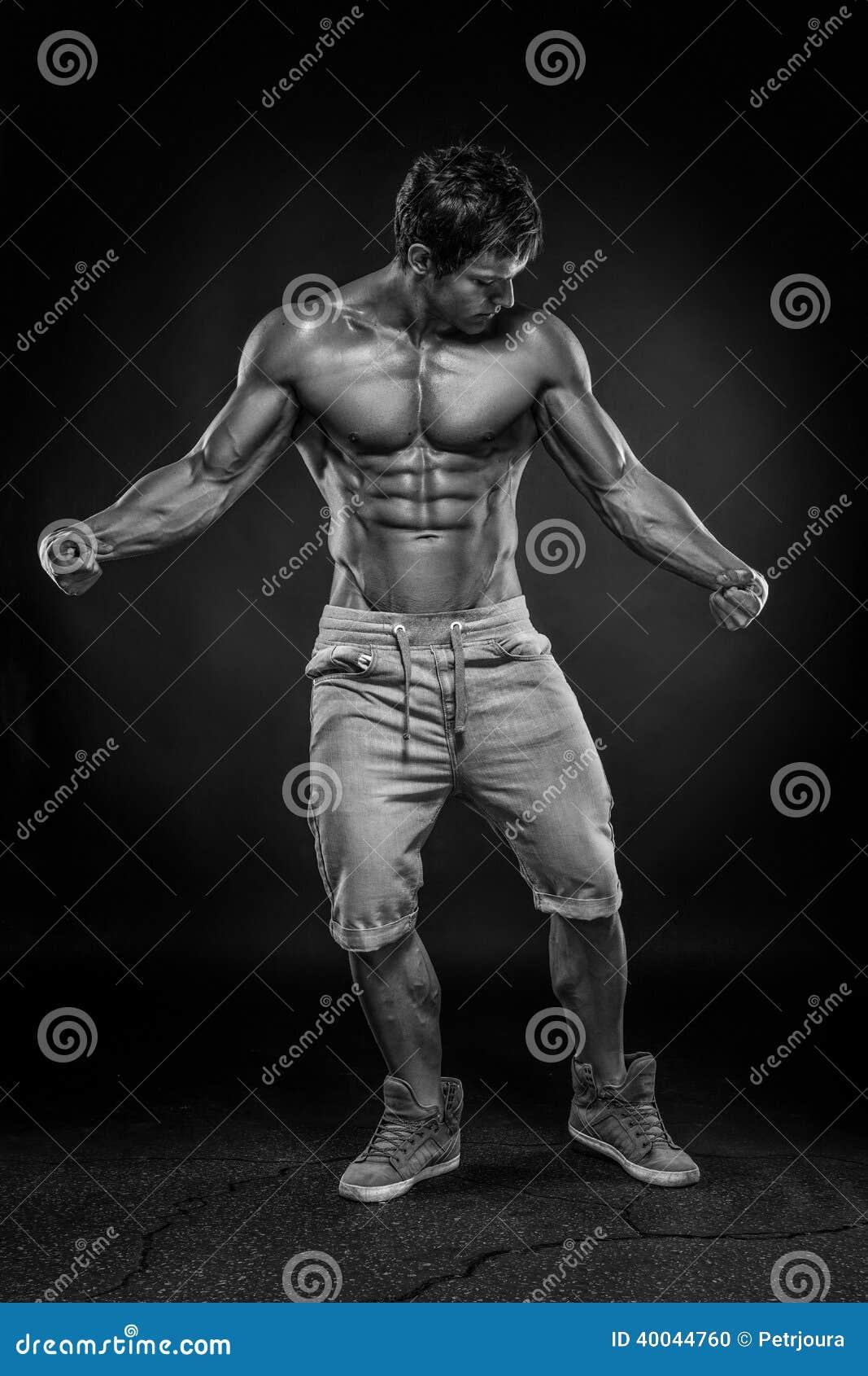 Сильный атлетический торс модели фитнеса человека показывая большие мышцы сверх