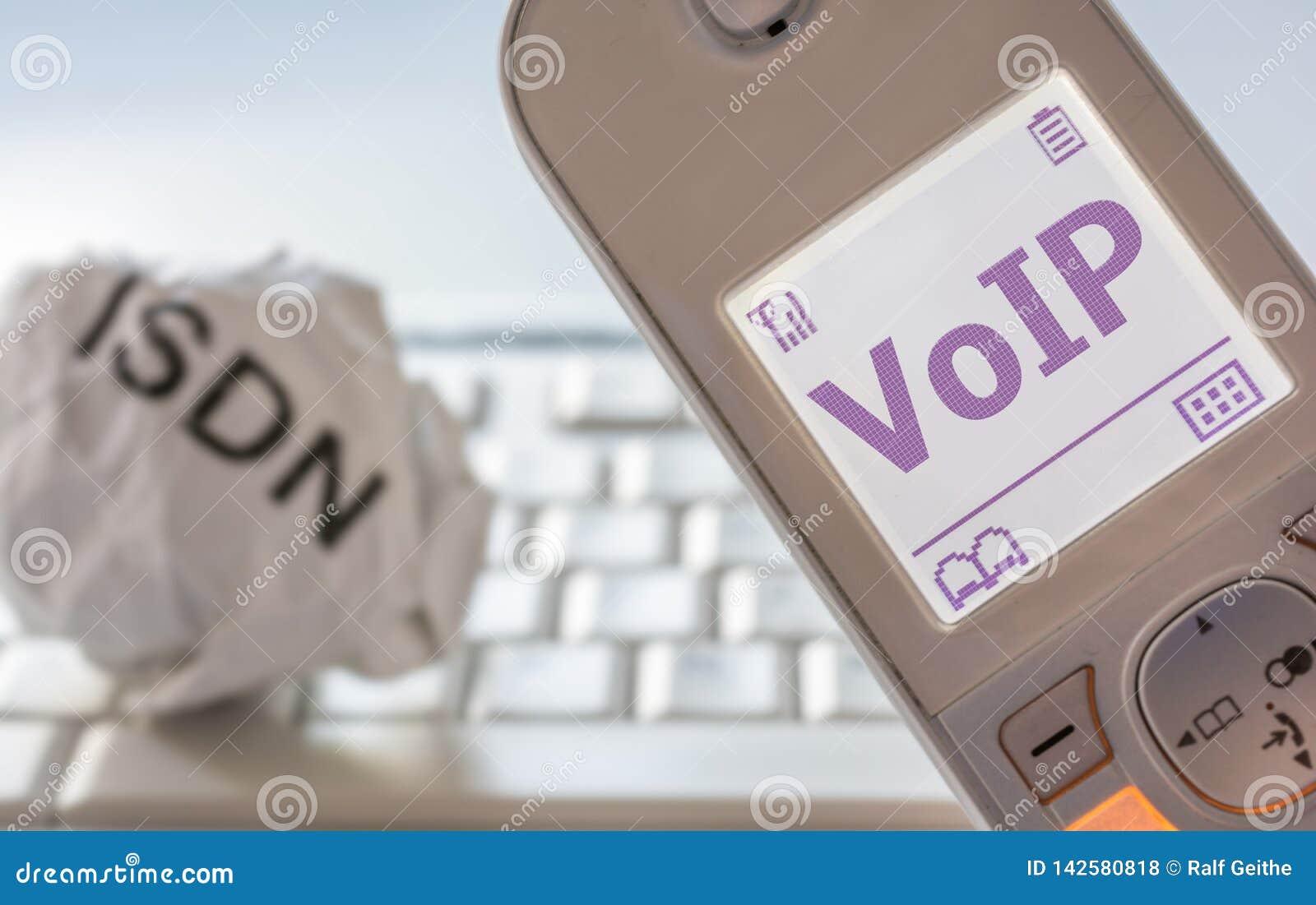 Скомканная бумага с надписью ISDN и современным телефоном с VoIP в дисплее