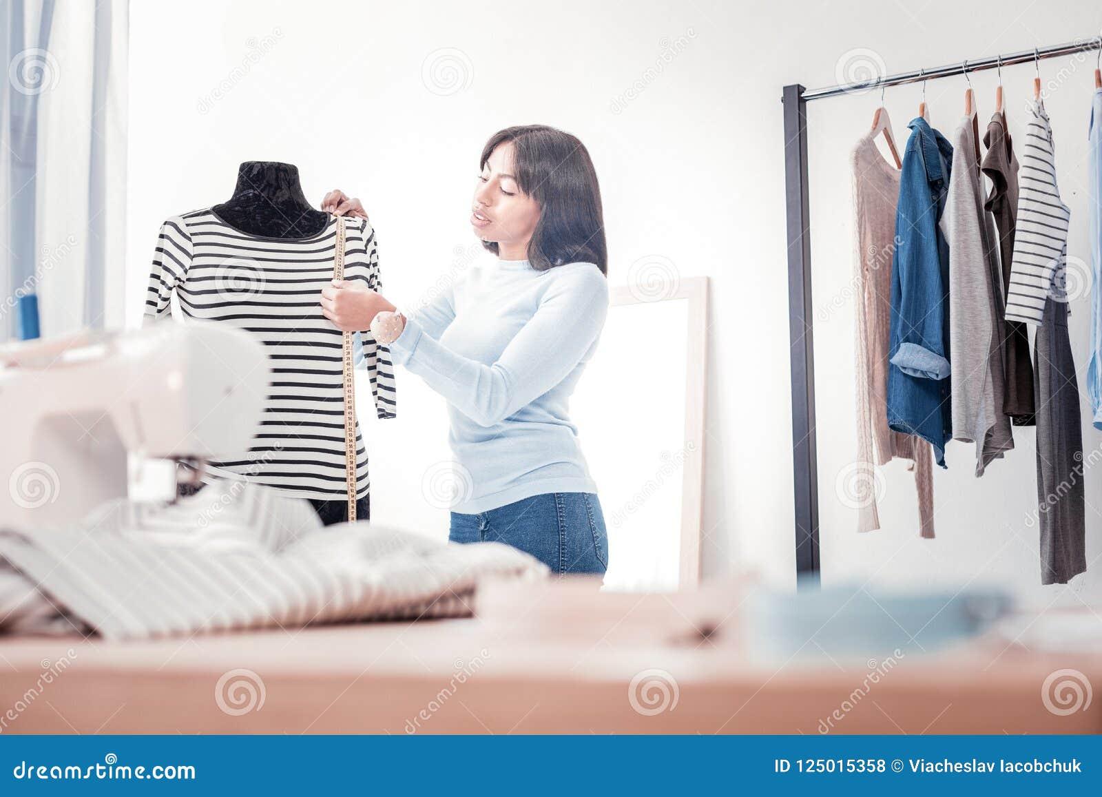 Сконцентрированный портной в процессе измеряя одежд