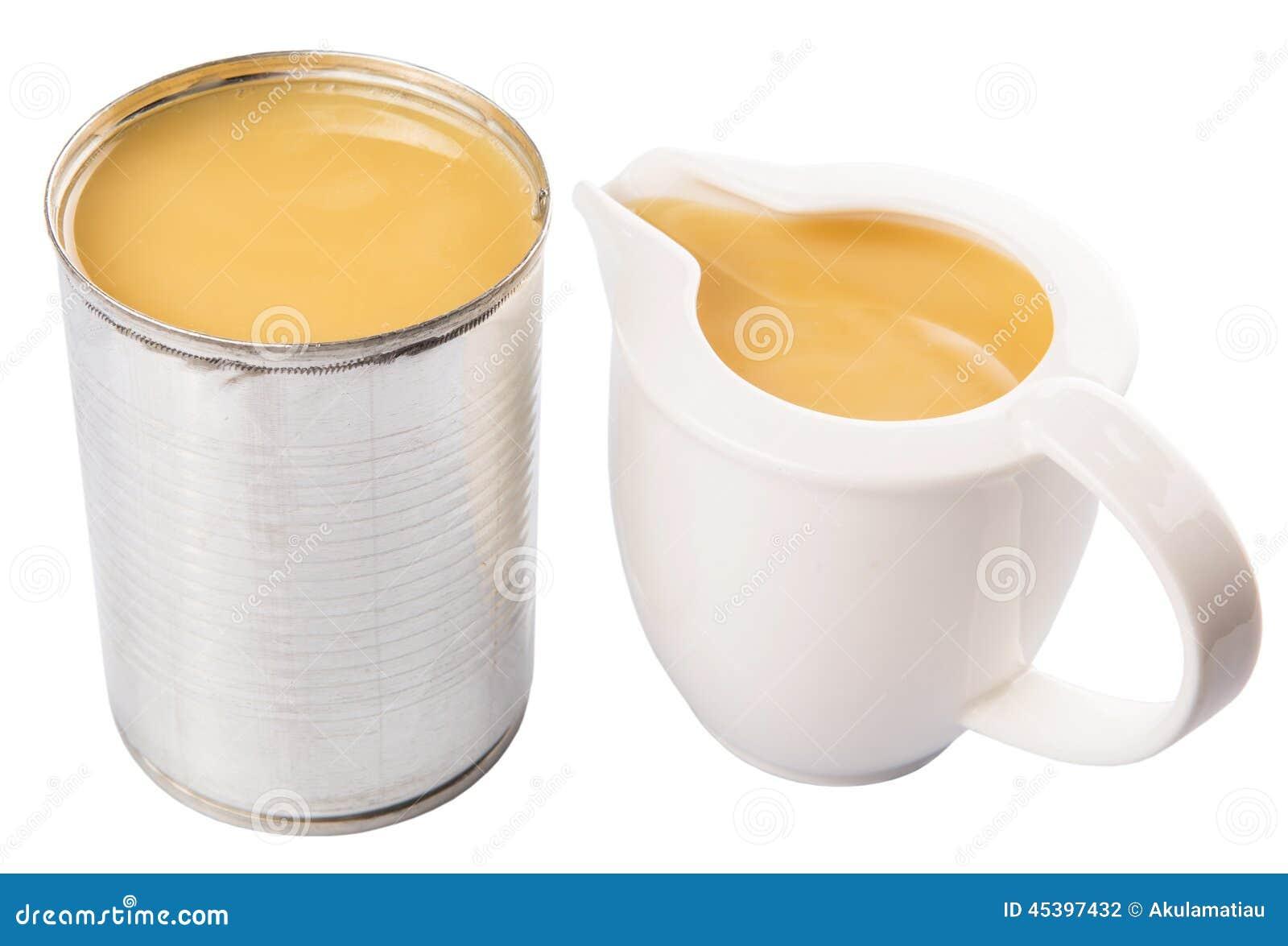 Сконденсированное молоко в контейнере i жестяной коробки и молока