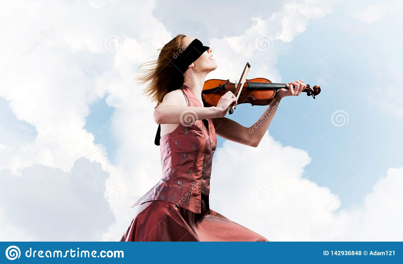 Скрипач женщины в красном платье играя мелодию против облачного неба