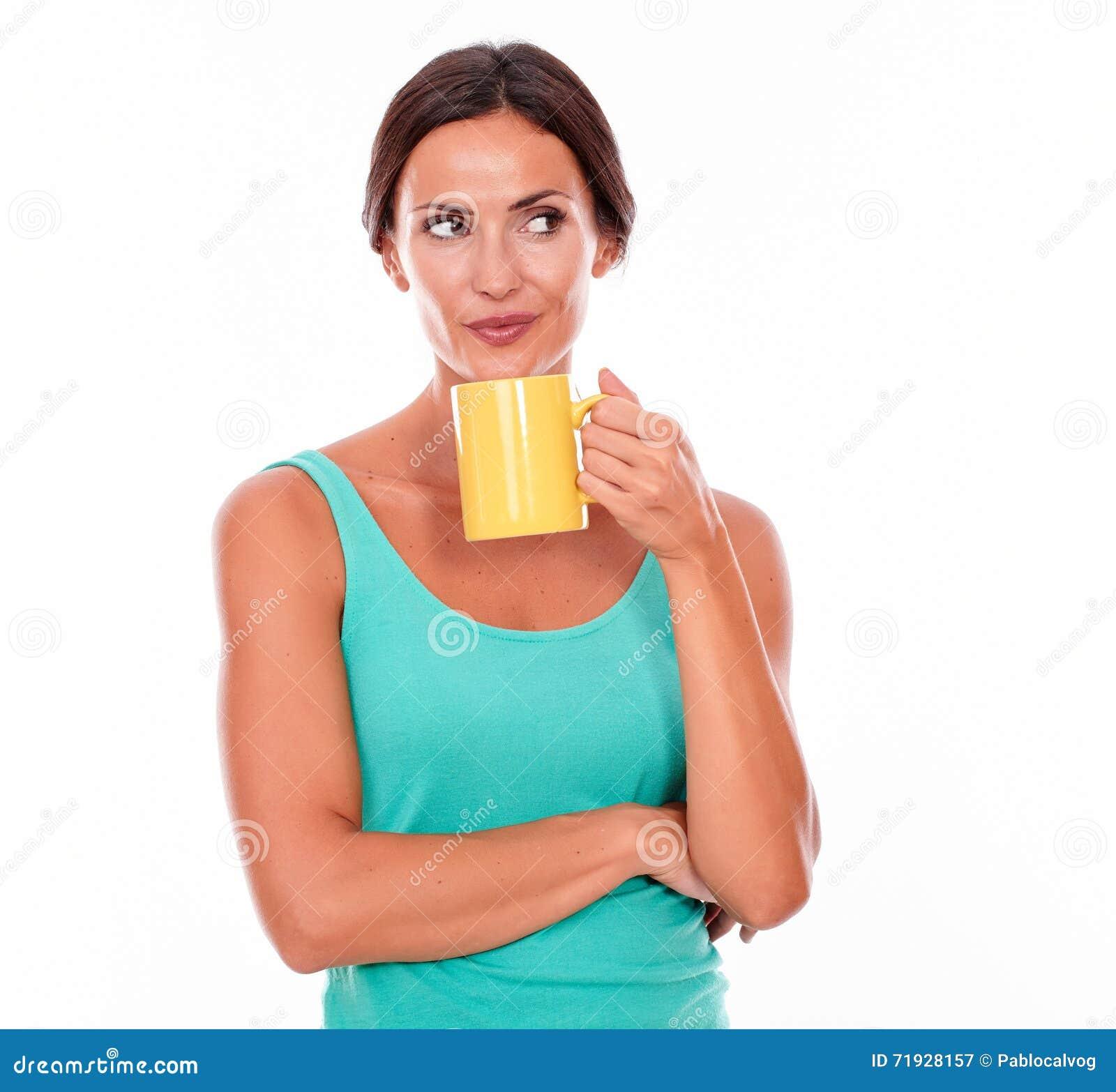 Скрытное усмехаясь брюнет с кружкой кофе