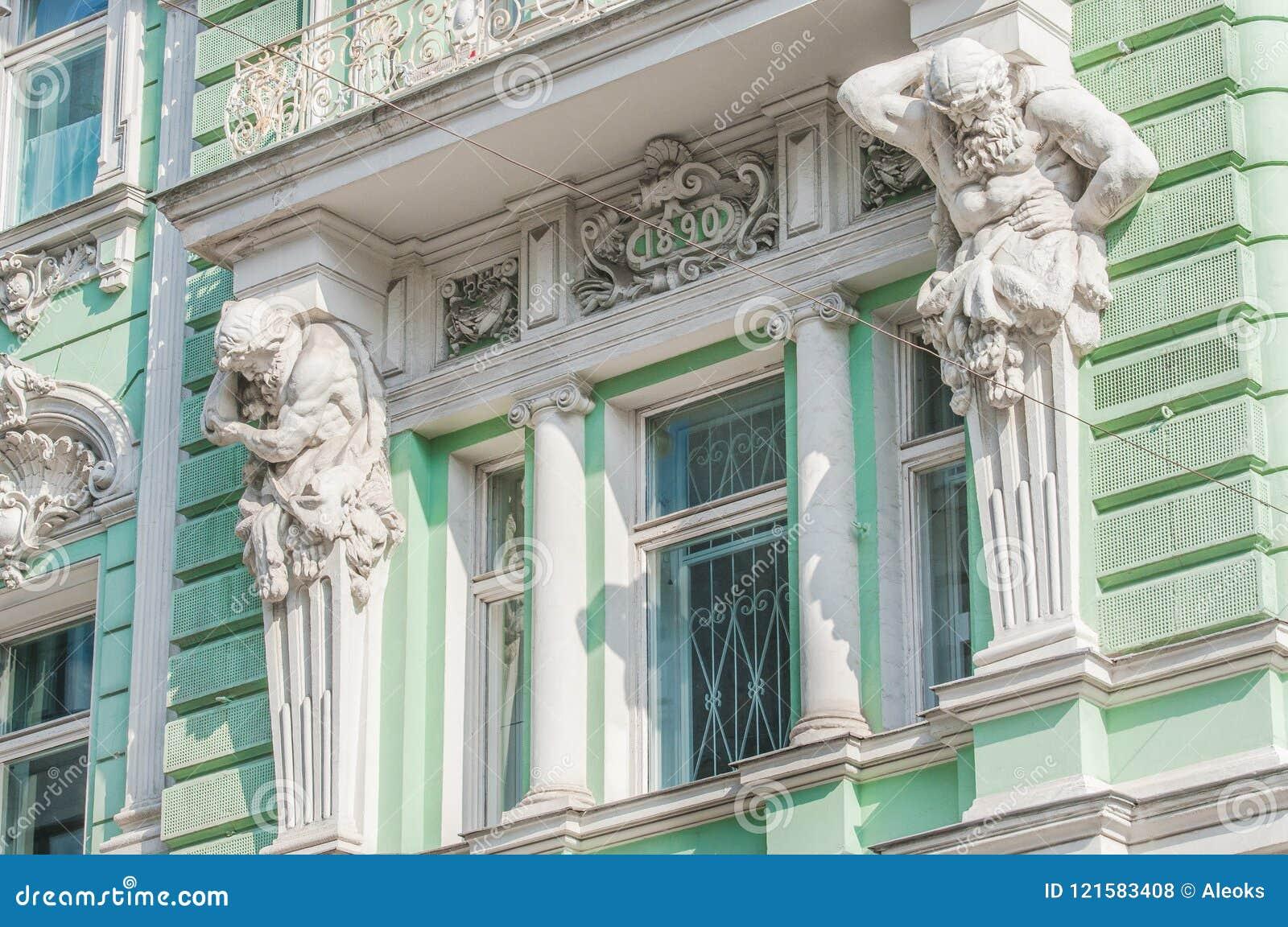 Скульптуры Atlantes на фасаде здания на улице Ilinka