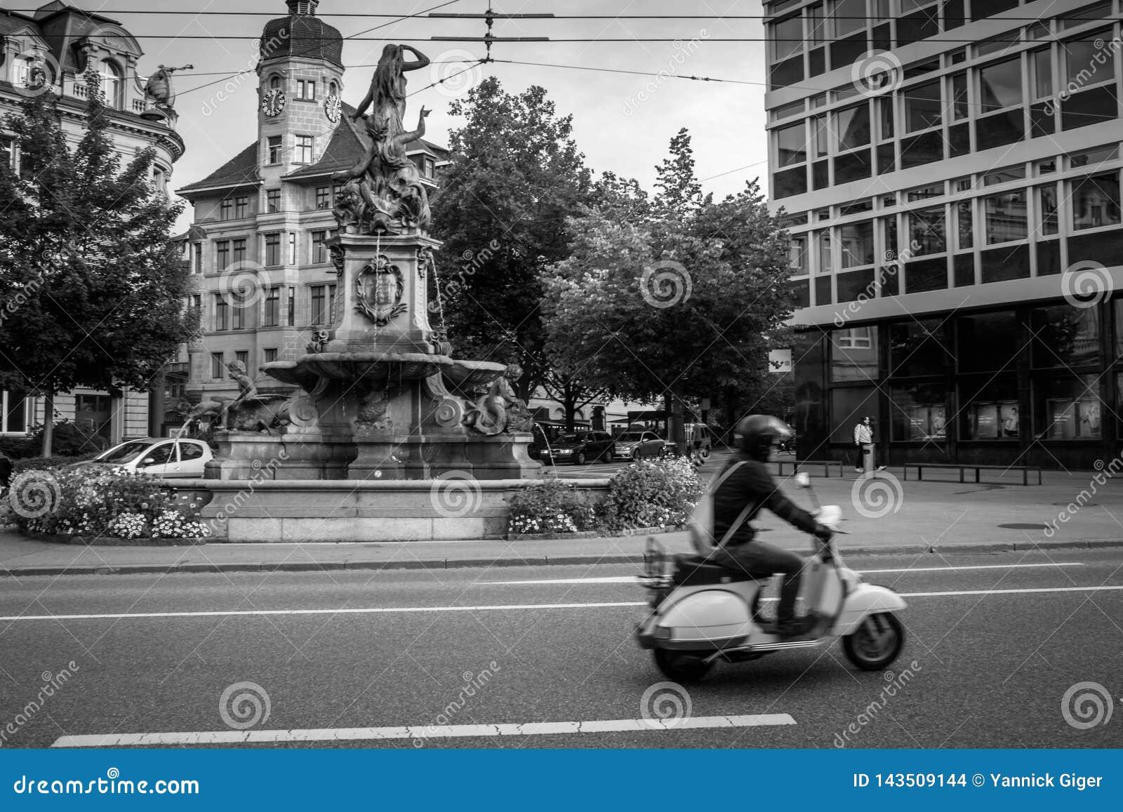 Скутер перед фонтаном в St Gallen, Швейцарии