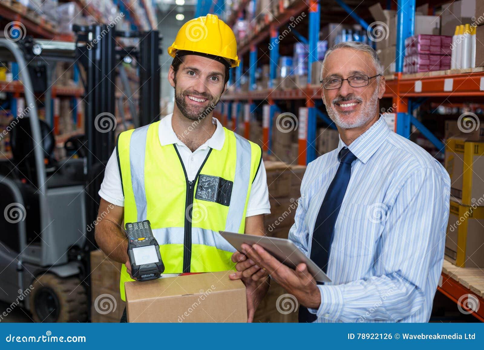 Складируйте менеджер держа цифровую таблетку пока мужской штрихкод скеннирования работника