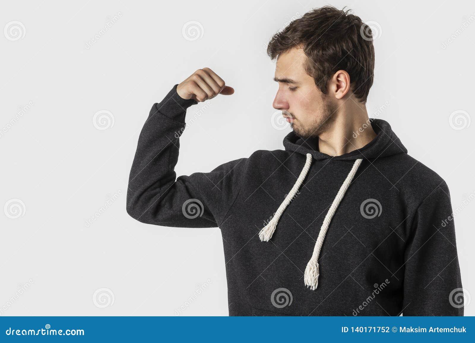 Слабый кавказский молодой человек смотрит его бицепс разочарованно белизна изолированная предпосылкой Концепция слабости