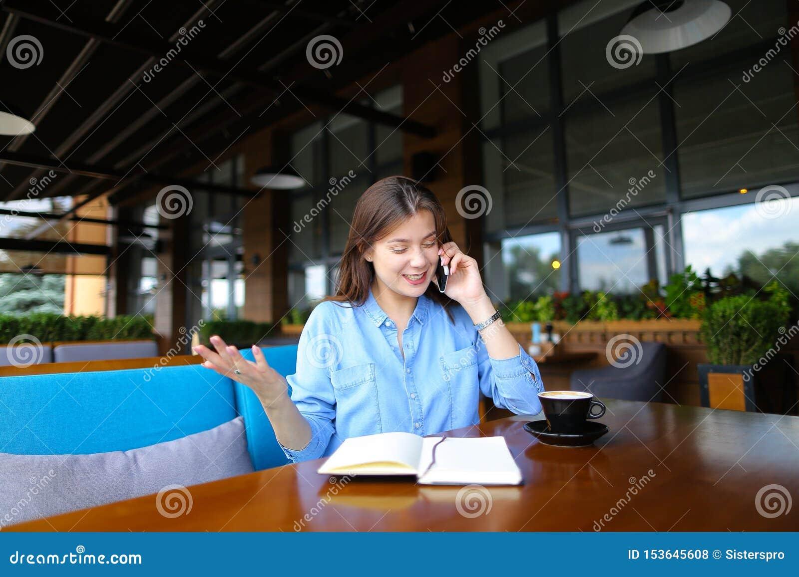 Славная студентка отдыхая на кафе с тетрадью и чашкой кофе, говоря смартфоном