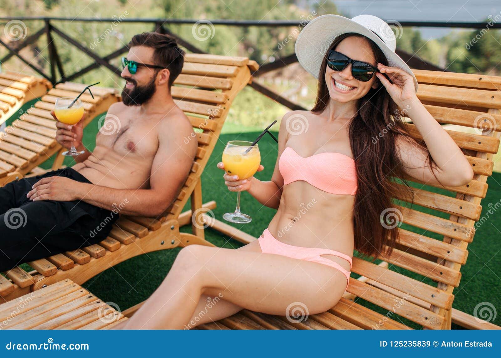 Славное изображение девушки и парня сидя на sunbeds Она смотрит на камере и улыбках Девушка касается ее солнечным очкам Она предс